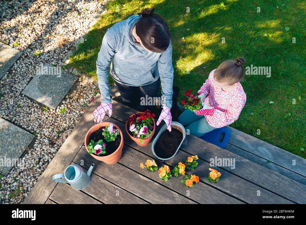 Mother and daughter planting flowers in pots in the garden - concept of working together, closeness, spending leisure time with family - view from abo Stock Photo