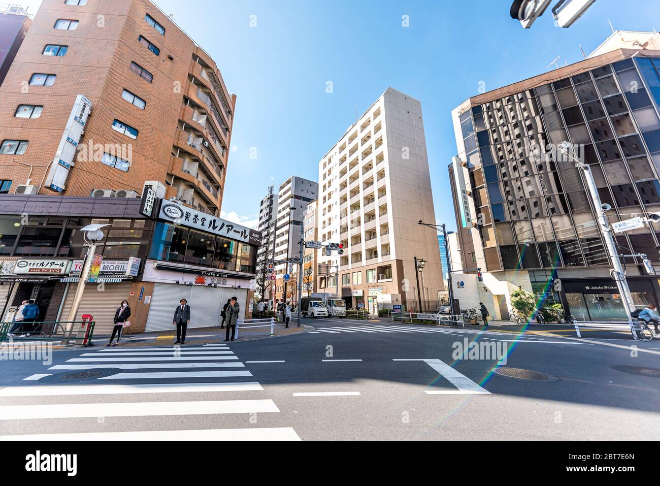 Tokyo, Japan - April 1, 2019: Shinjuku street with people waiting at crosswalk in morning commute on road wide angle view with flare Stock Photo