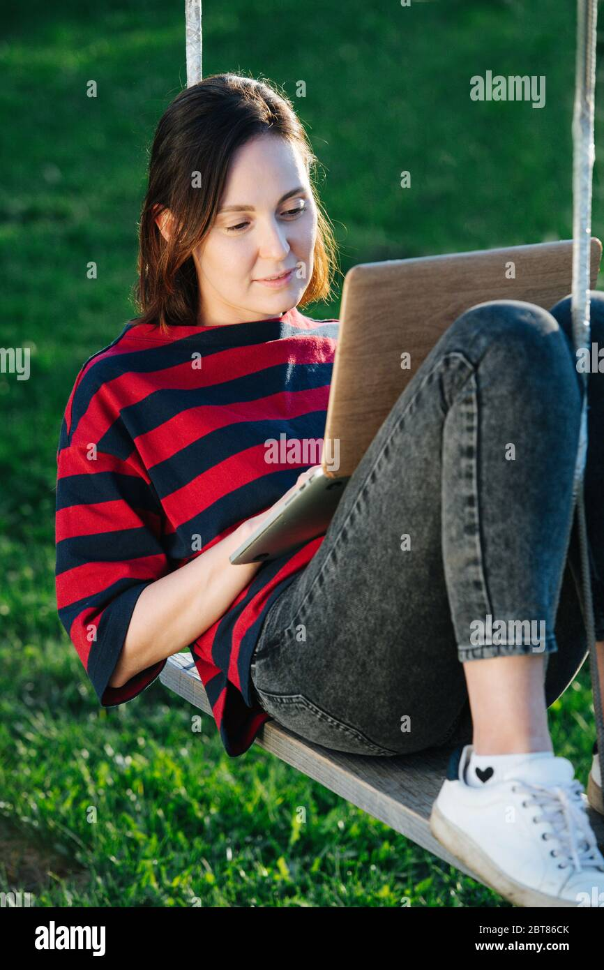 Peaceful happy young woman sitting comfortably on the swings with laptop Stock Photo