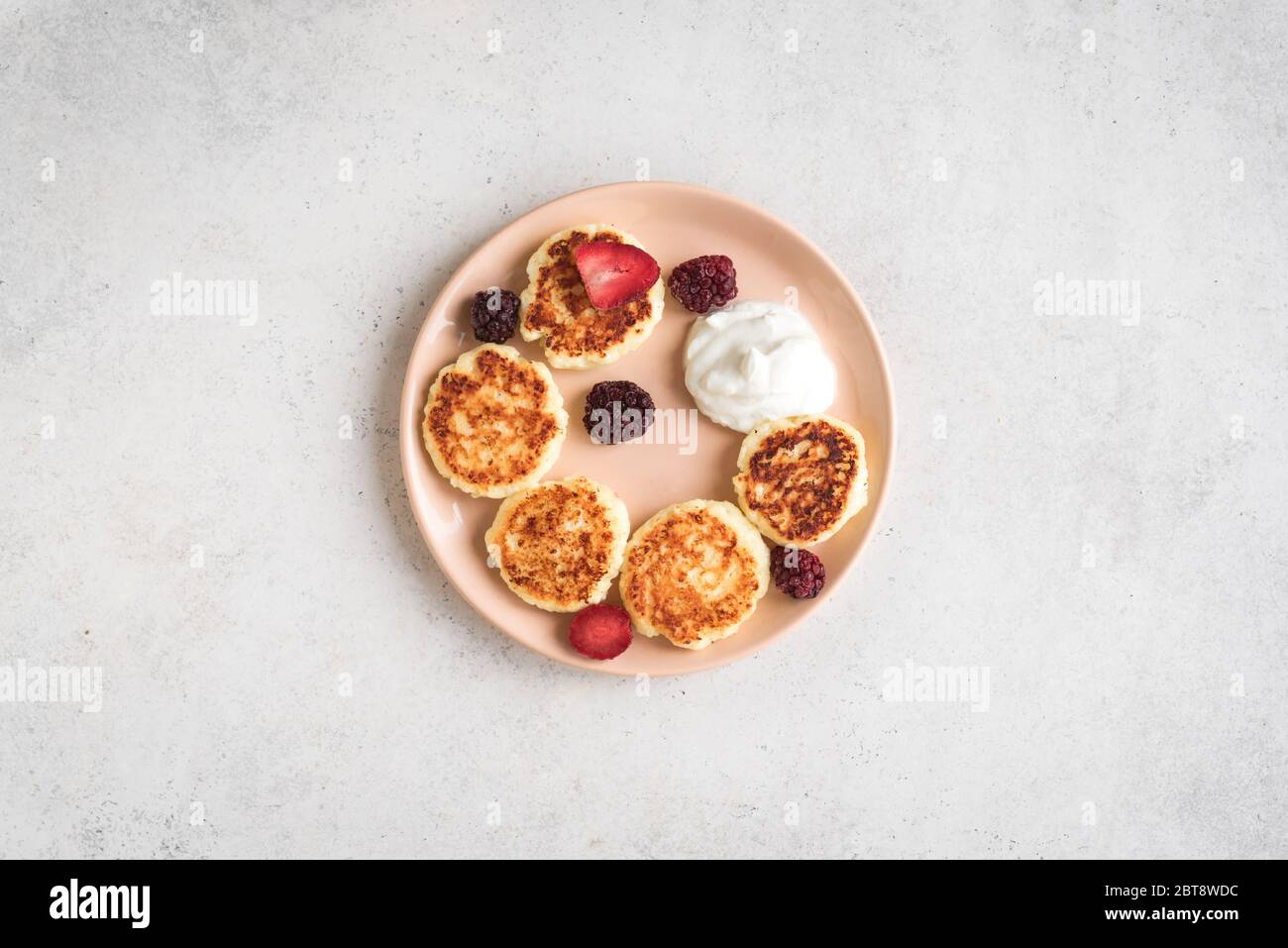 Cottage cheese pancakes  (syrniki, curd fritters) for breakfast. Fresh homemade cheese pancakes on white background, top view, copy space. Stock Photo