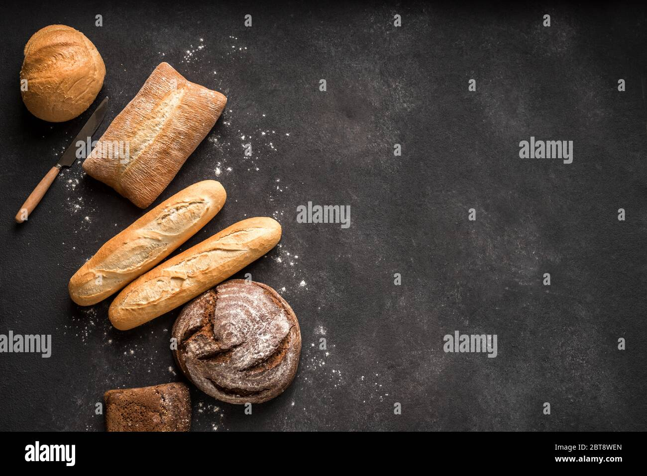 Fresh Bread on black background, top view, copy space. Homemade fresh baked various loafs of wheat and rye bread close up. Stock Photo