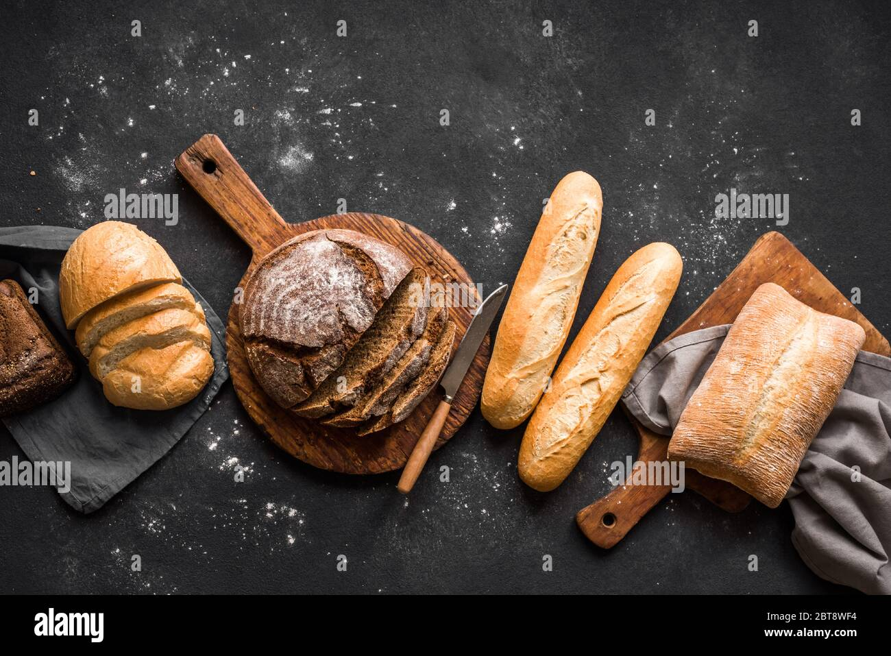 Fresh Bread on black background, top view, copy space. Homemade fresh baked various loafs of wheat and rye bread flat lay. Stock Photo