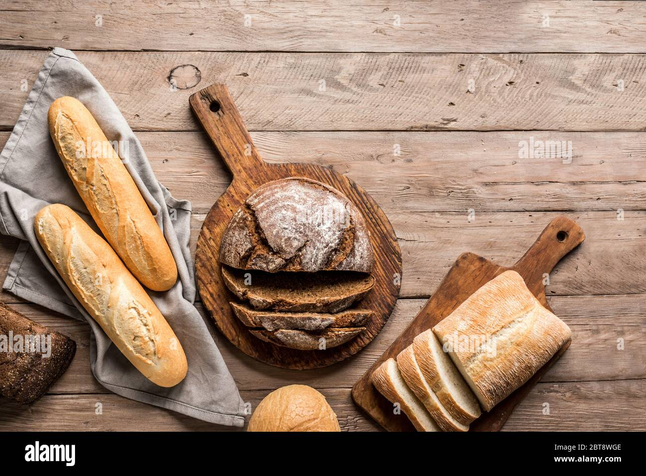 Fresh Bread on wooden background, top view, copy space. Homemade fresh baked various loafs of wheat and rye bread flat lay. Stock Photo