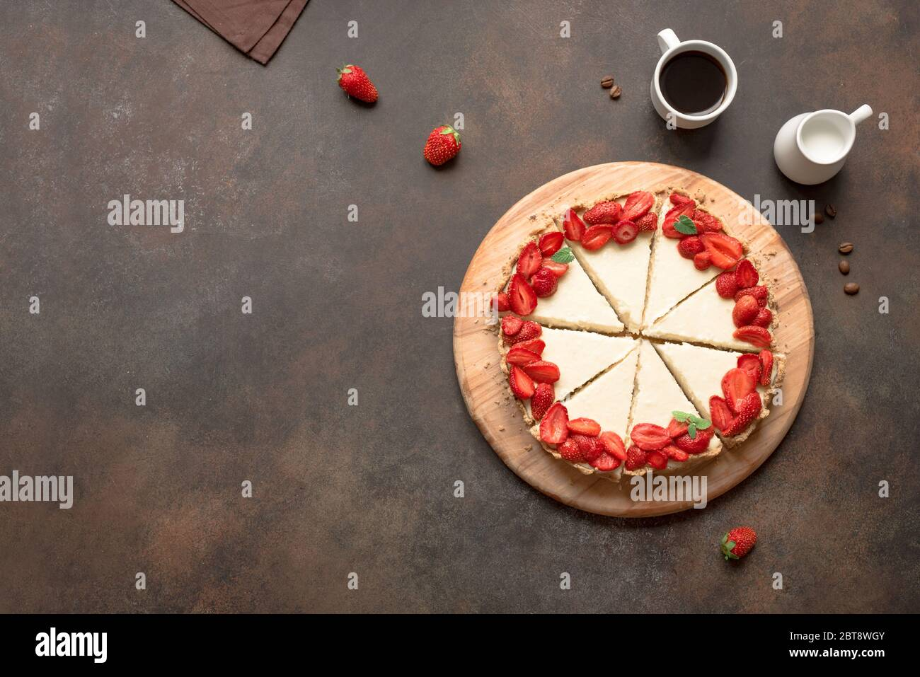 Cheesecake with strawberries and coffee, top view, copy space. Slice of homemade cheese cake and sauteed berries, delicious desert. Stock Photo