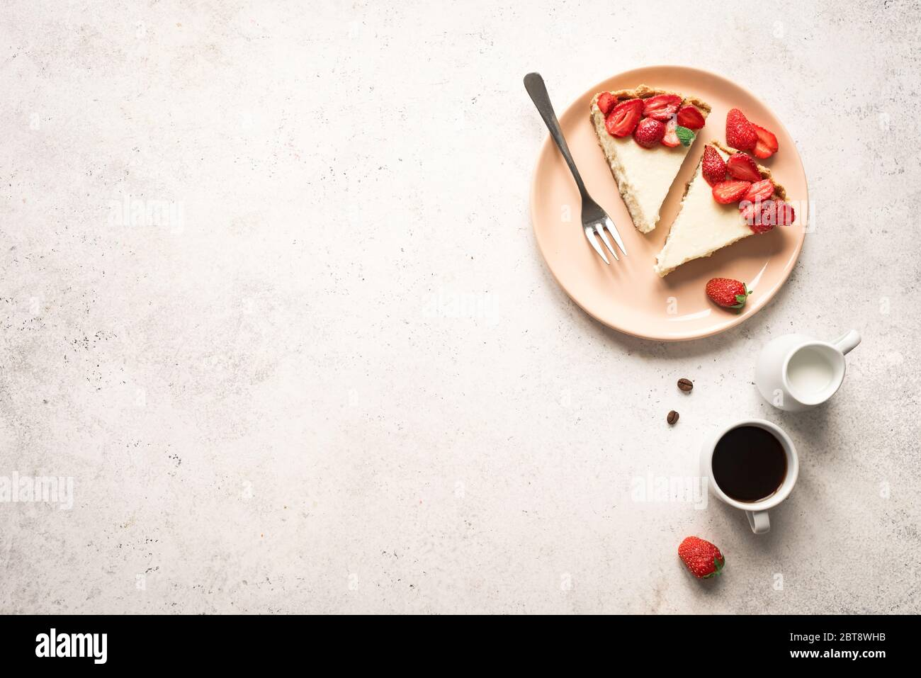 Cheesecake with strawberries on plate, top view, copy space. Slice of homemade cheese cake and sauteed berries, delicious desert. Stock Photo
