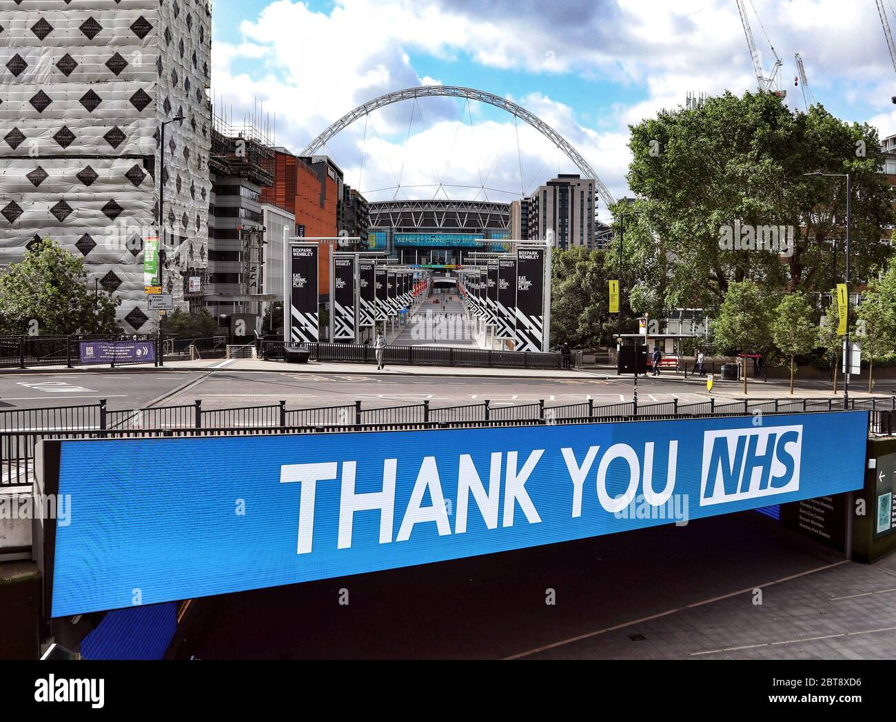 Day Sixty One of Lockdown, in London. A Thank you NHS sign on the bridge over Wembley Way, which is almost empty of people, when normally it would have seen tens of thousands of football fans going to the showpiece of the English football season. Today would have seen the Emirates FA Cup Final being played at Wembley Stadium, but due to the Coronavirus pandemic, it has been postponed. Even though there has been a partial lifting of lockdown, there are still many shops that have to remain closed, including barbers and hairdresser salons, but more people seem to be out and about on the streets a Stock Photo