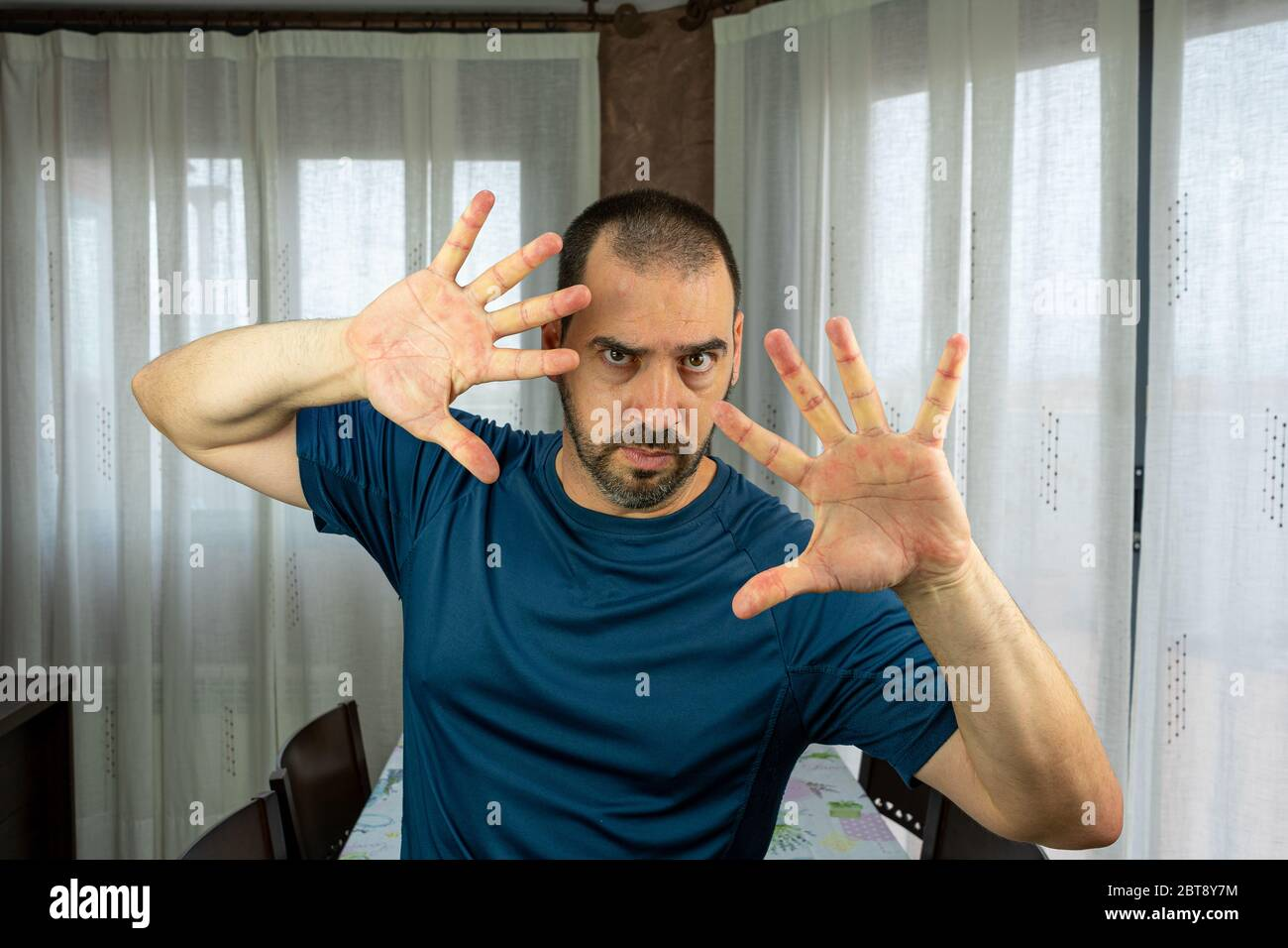 Bearded Man With Short Hair Dressed In A Dark Blue Shirt With Raised Hands As A Sing Of Protection In The Living Room At Home Security Concept Stock Photo Alamy