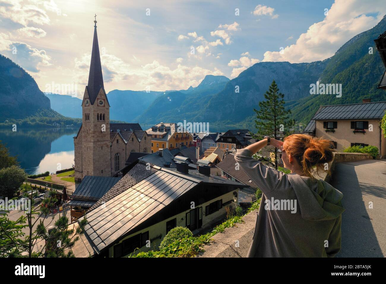 Female tourist looking at stunning Hallstatt, Salzkammergut region, OÖ, Austria, from an elevated viewing point above the roofs of the famous village Stock Photo
