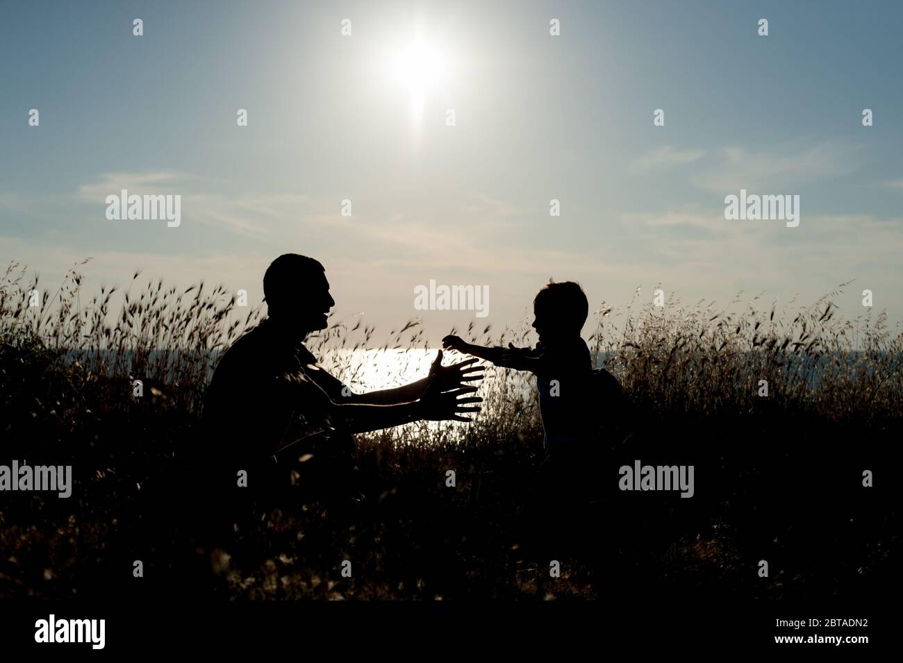 love embrace concept of young family little son running to his father open arms outdoor sea sunset Stock Photo