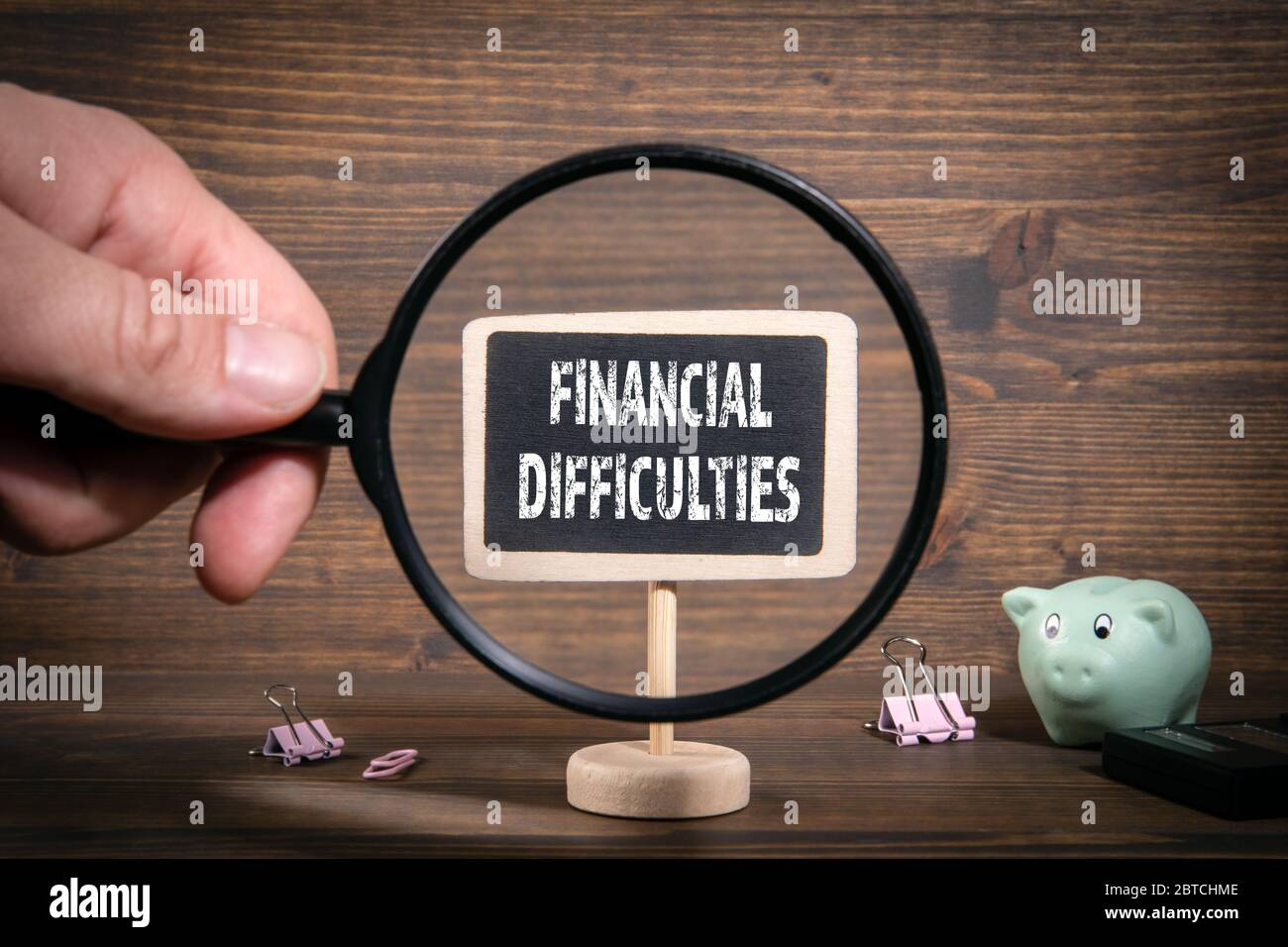 FINANCIAL DIFFICULTIES. Crisis, recession, support and credit holidays concept. Man's hand, holding magnifying glass Stock Photo