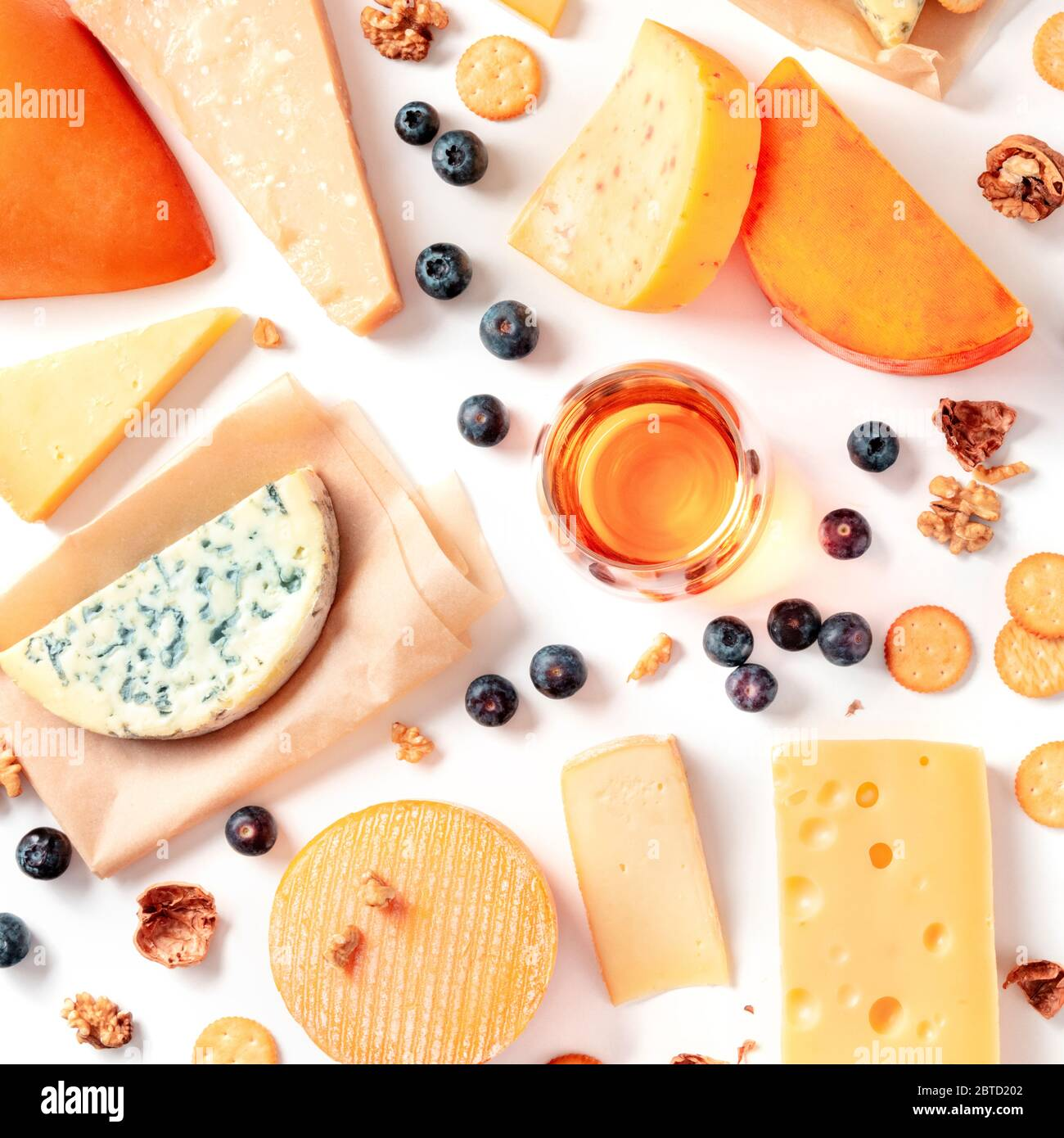 Cheese and wine tasting and pairing flat lay on a white background. Many different cheeses, overhead square shot Stock Photo