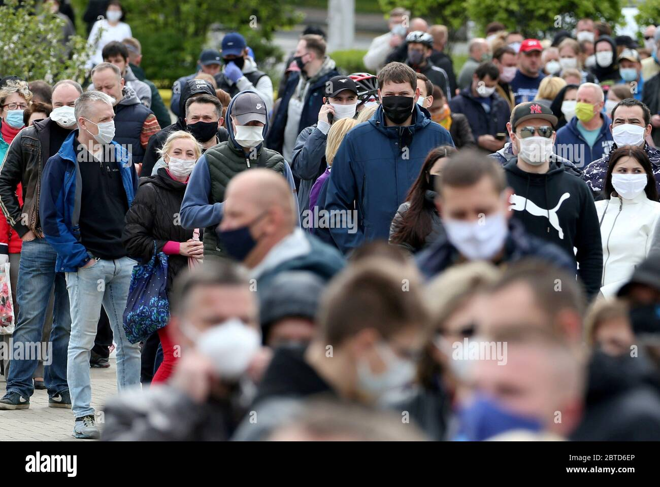 Minsk, Belarus. 24th May, 2020. People in face masks queue to add their signatures in support of presidential candidate Svetlana Tikhanovskaya (not pictured) during a rally outside Komarovsky Market organised by activists to collect signatures in support of 15 presidential hopefuls. The campaign in support of potential presidential candidates started on 21 May. Belarus is to hold a presidential election on 9 August 2020. Credit: Natalia Fedosenko/TASS/Alamy Live News Stock Photo