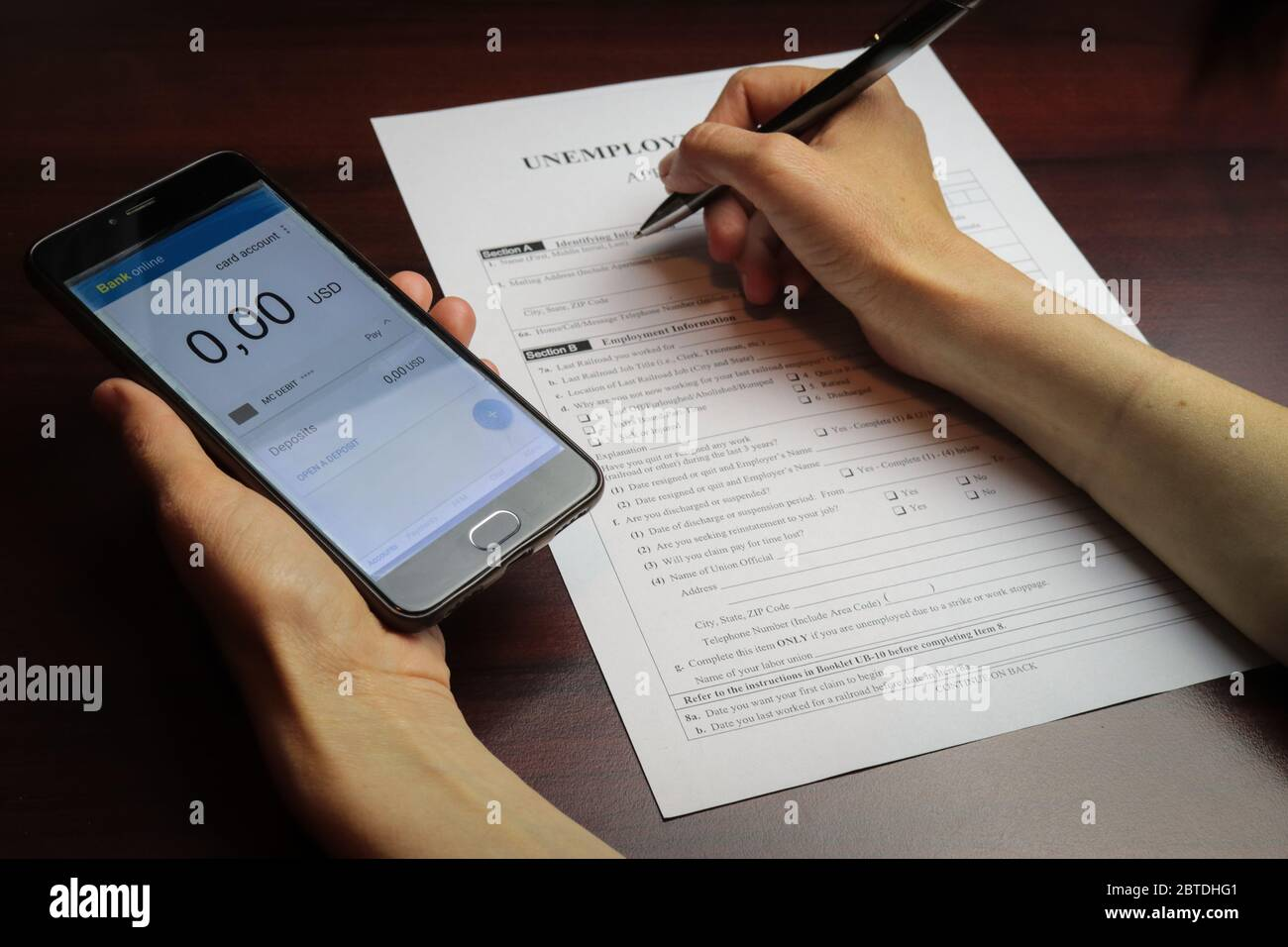 A woman checks her account balance on phone. Lack of money, filling out unemployment benefits form.  All screen graphics are made up. Concept of coron Stock Photo