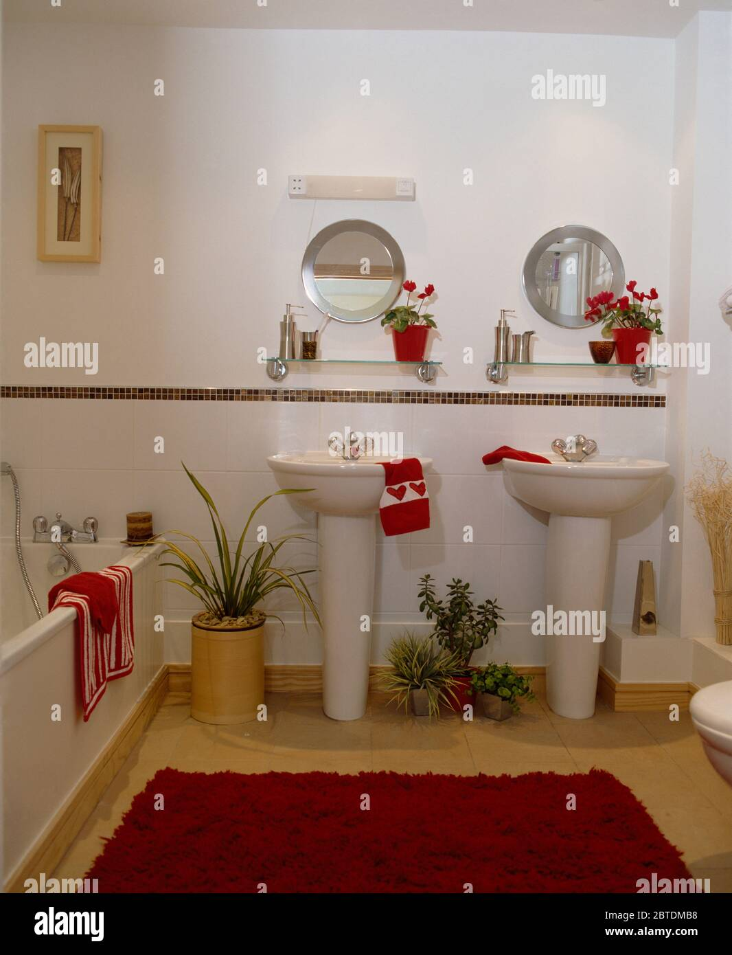 Double Pedestal Basins In White Bathroom With Red Accents Stock Photo Alamy