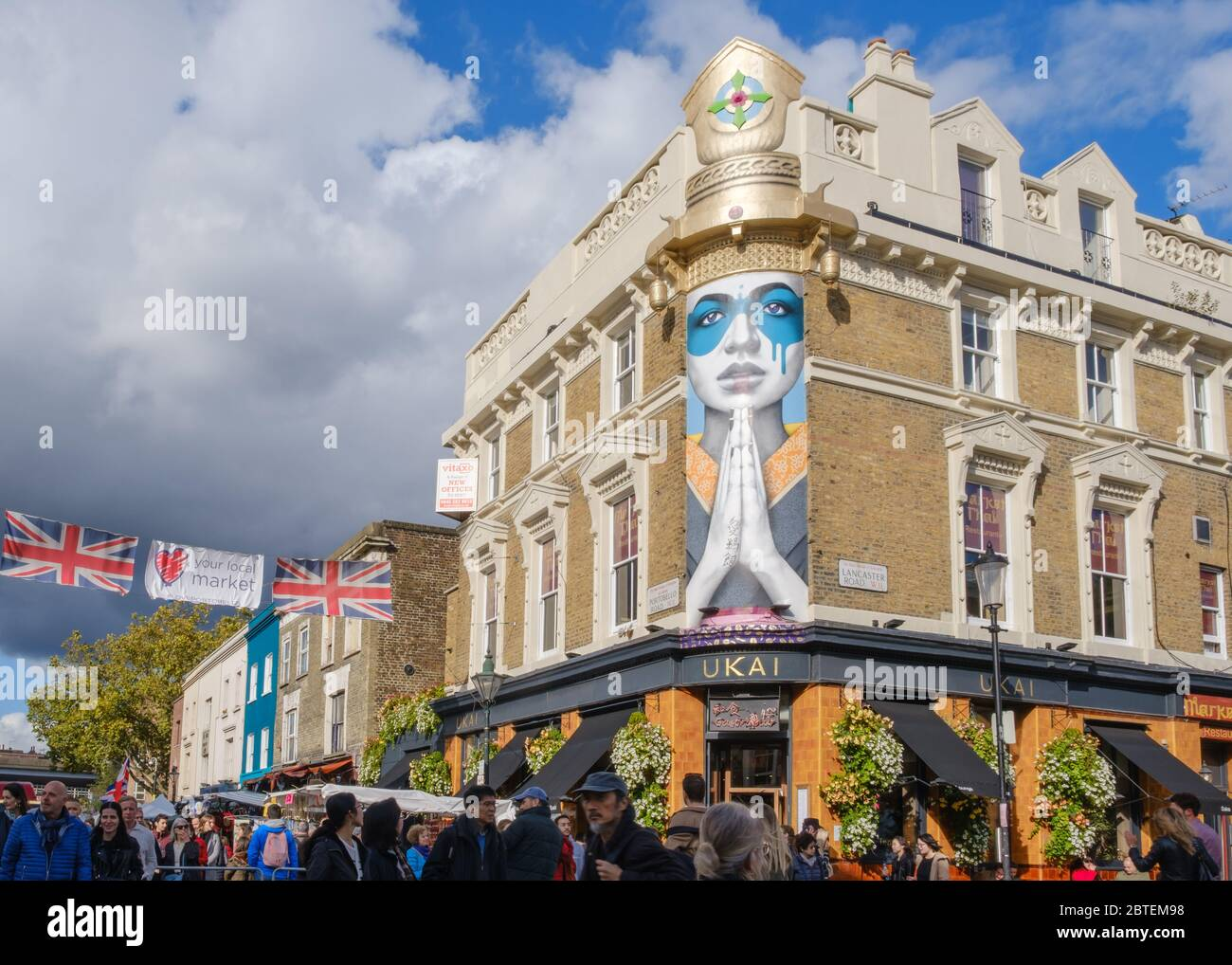 Crowds Of People Shopping At Portobello Road Market With Japanese Restaurant Ukai Mural Street Art Lady Kinoko By Fin Dac In Background Stock Photo Alamy
