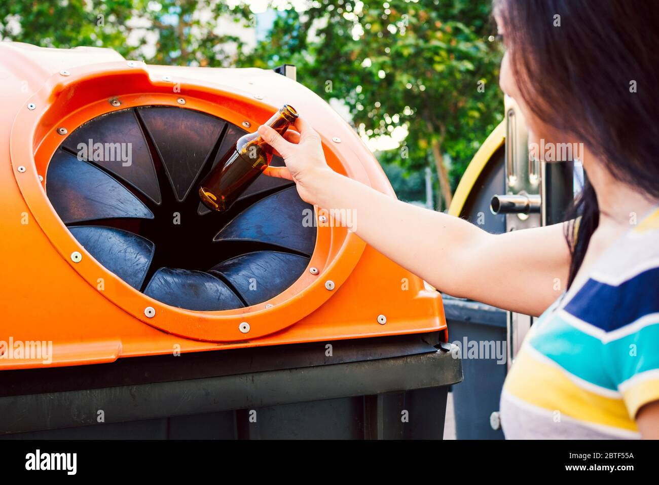 Close-up of woman putting glass bottle into bottle bank. Recycling concept Stock Photo