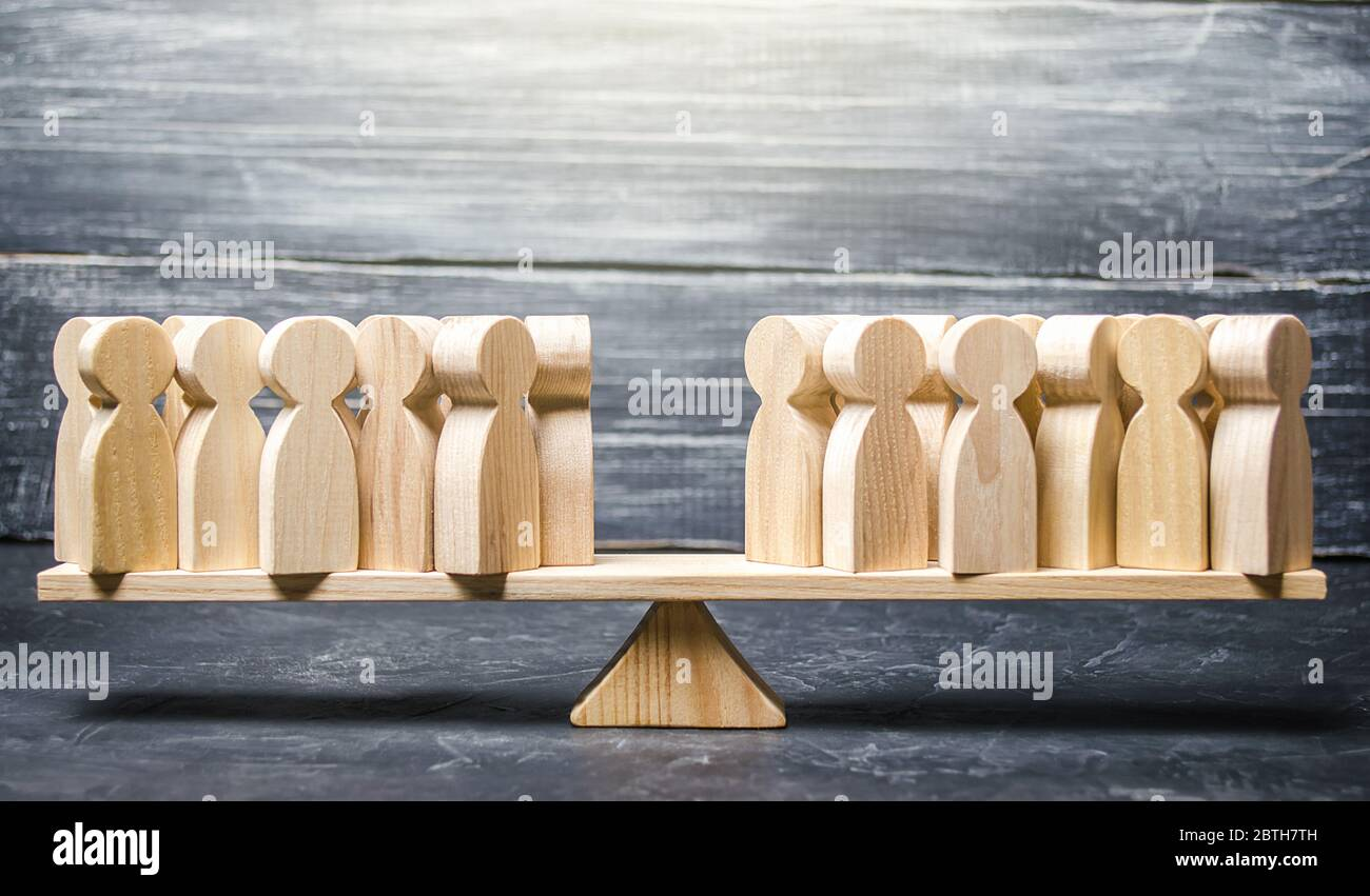 Two groups of people on the scales. Two groups of people on the back of the scale. Different opinions, opposition and opposition in society. Disagreem Stock Photo