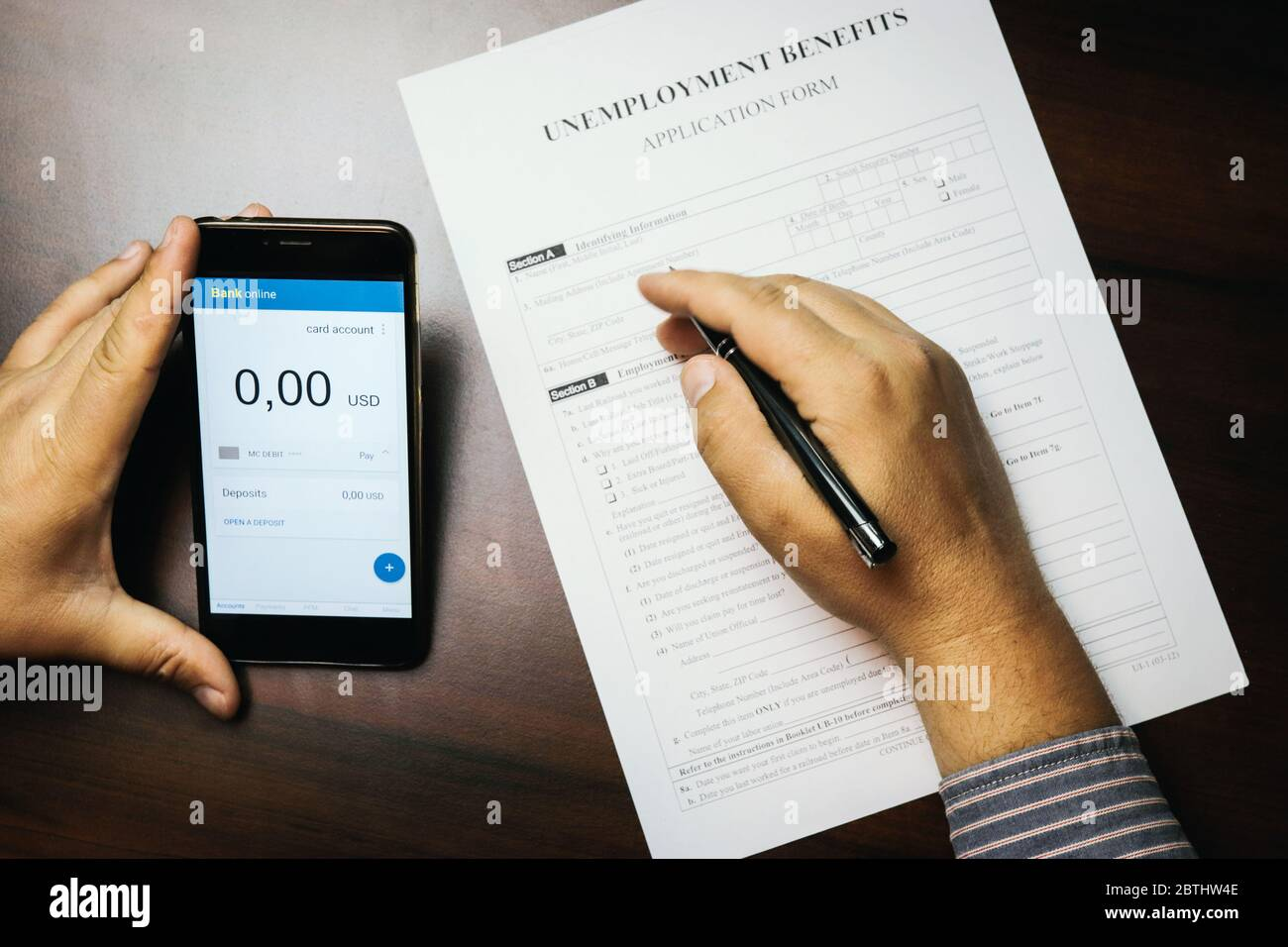 A man checks her account balance on phone. Lack of money, filling out unemployment benefits form.  All screen graphics are made up. Concept of coronav Stock Photo