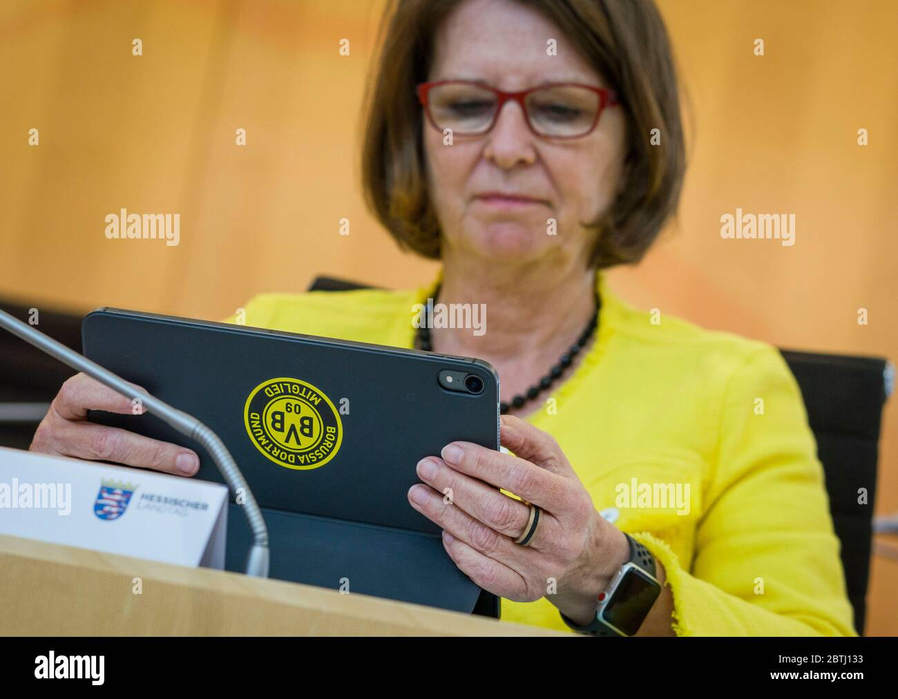 Wiesbaden, Germany. 26th May, 2020. Priska Hinz, the Hessian Minister for Environmental Protection, Agriculture and Consumer Protection (Greens), sits with her laptop on the government bench during the plenary debate in the Hessian state parliament. It bears a sticker with the logo of Borussia Dortmund, the Bundesliga football club. The minister is a member of the club. Credit: Frank Rumpenhorst/dpa/Alamy Live News Stock Photo