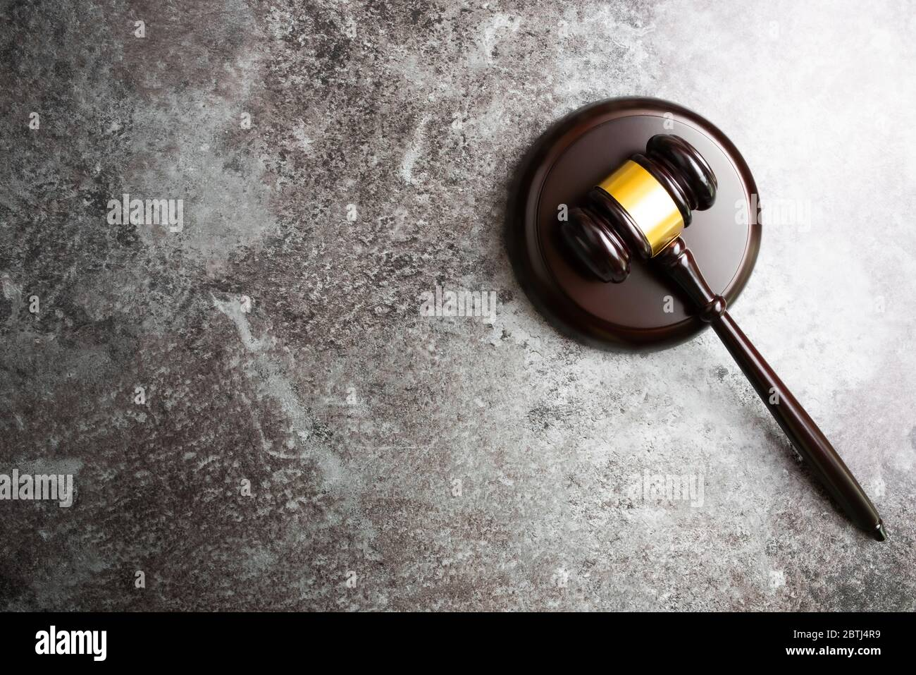 directly above view of judges gavel on marble stone table background Stock Photo