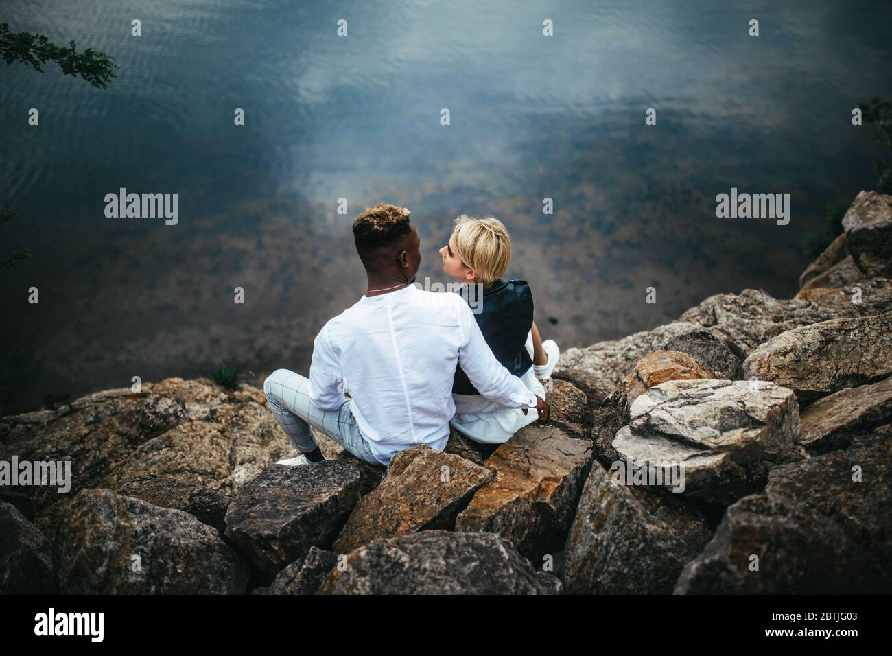 Interracial couple sits on rocks and hugs against background of river. Concept of love relationships and unity between different human races. Stock Photo