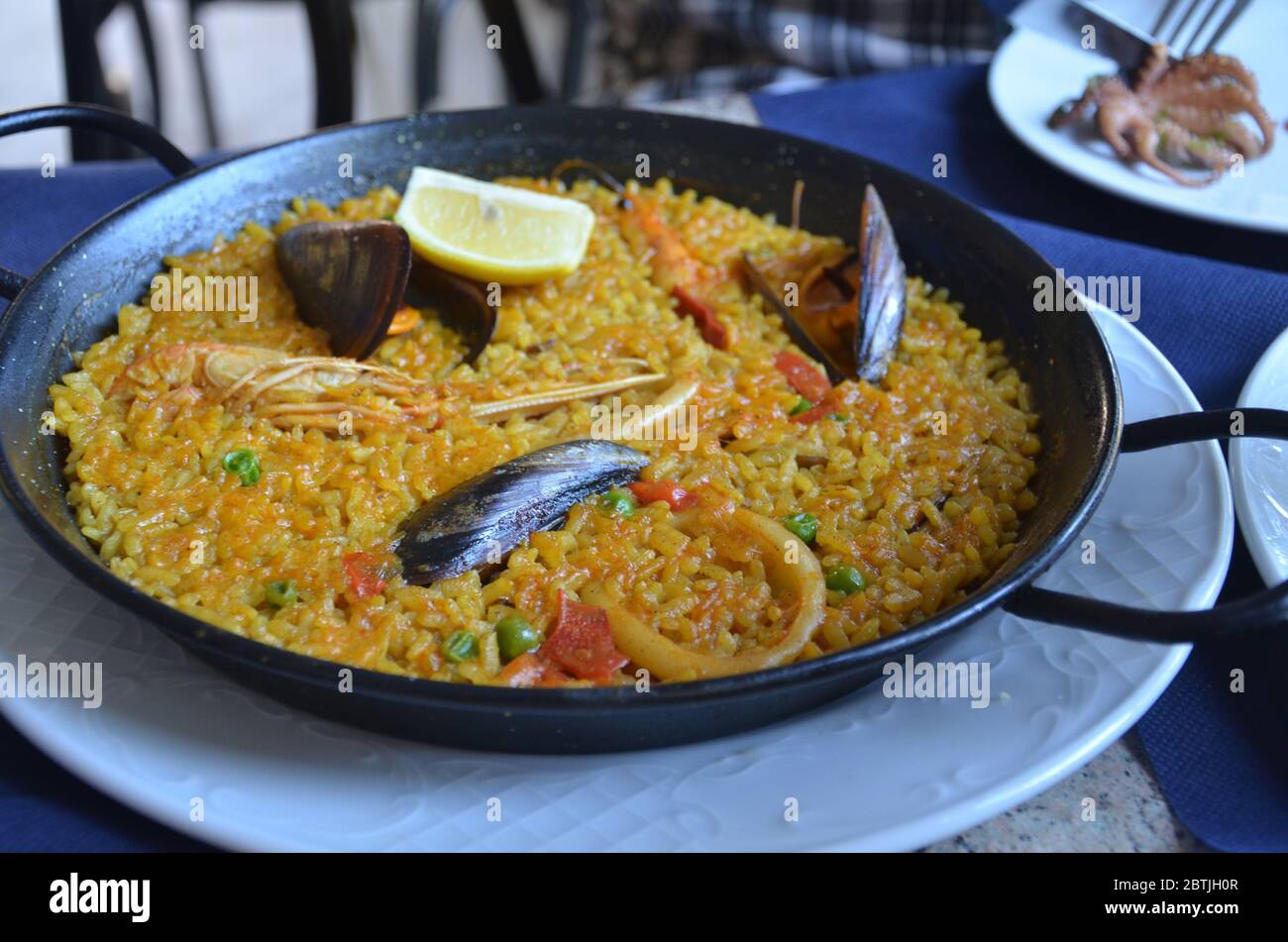 Paella is a Spanish rice dish originally from Valencia. Seafood paella from a local cafe at Barcelona. Stock Photo
