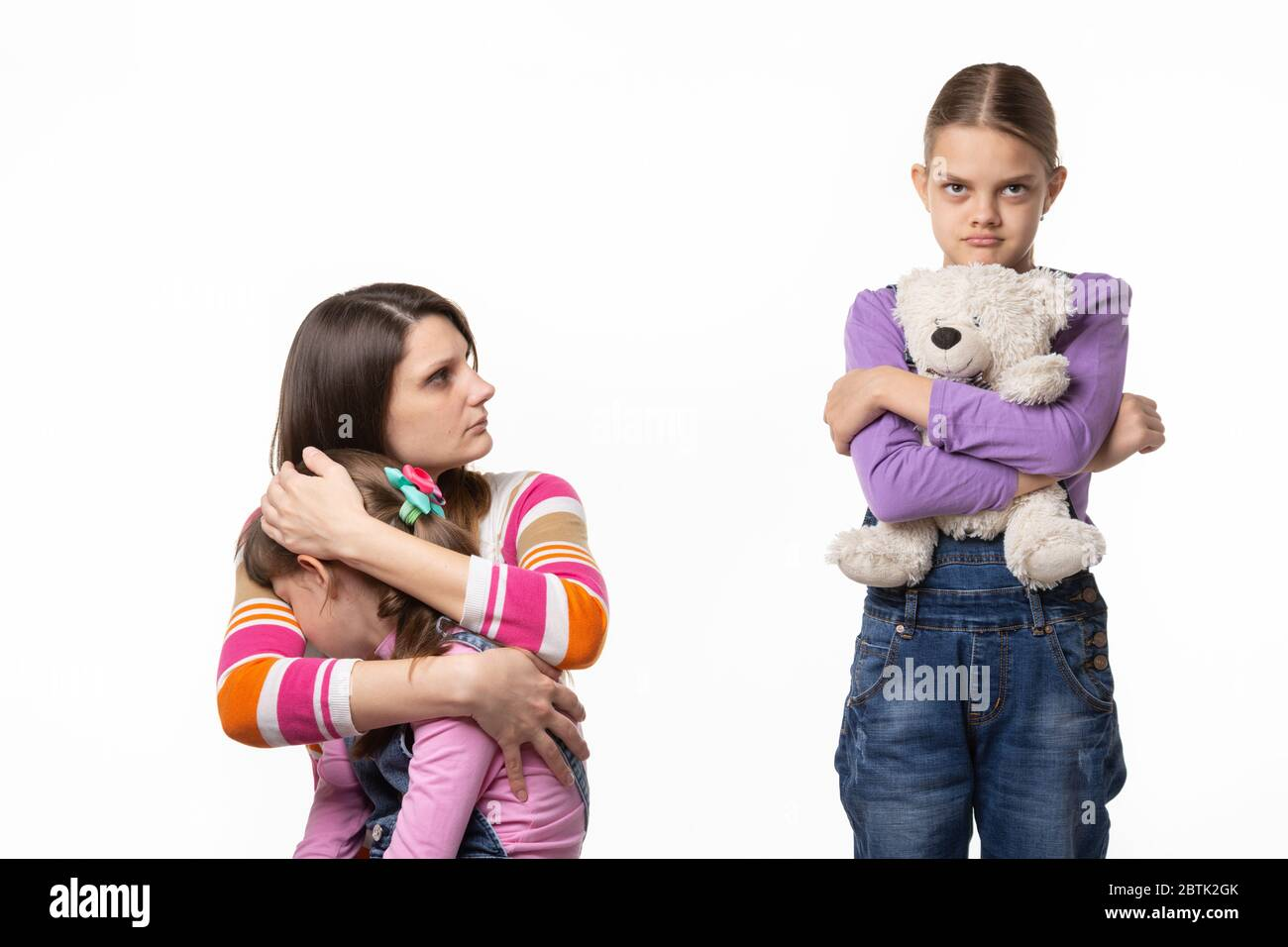 Mom reproachfully looks at the eldest daughter for offending the younger daughter Stock Photo