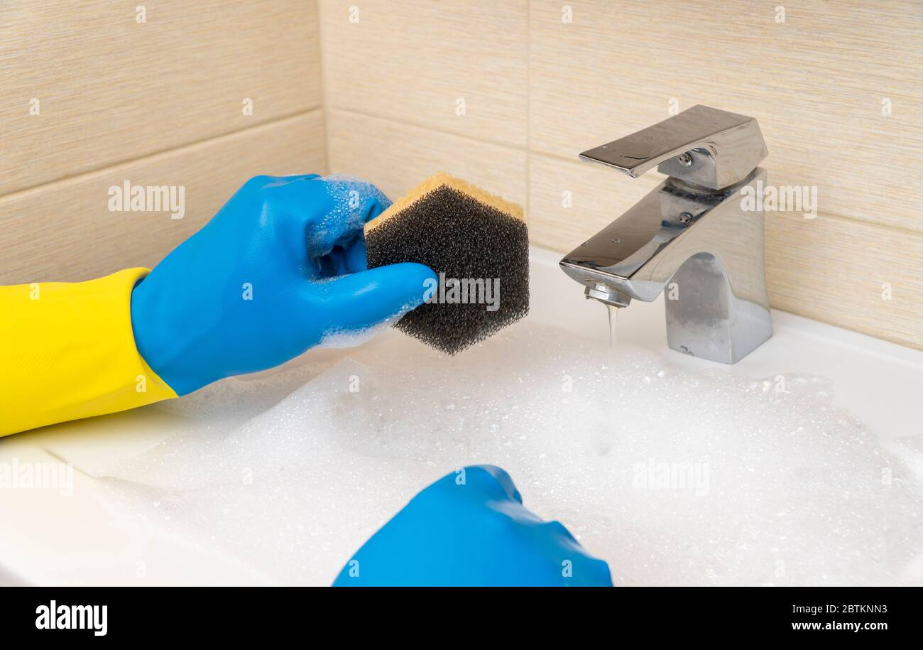 cleaning the bathroom. hand in a rubber glove washes the wash basin with detergents. Stock Photo