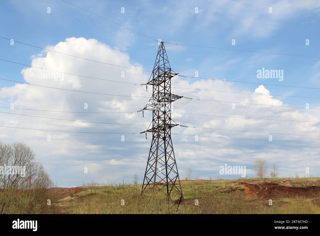 Iron pylon of a high voltage power line stands in a field against a blue sky. Stock Photo