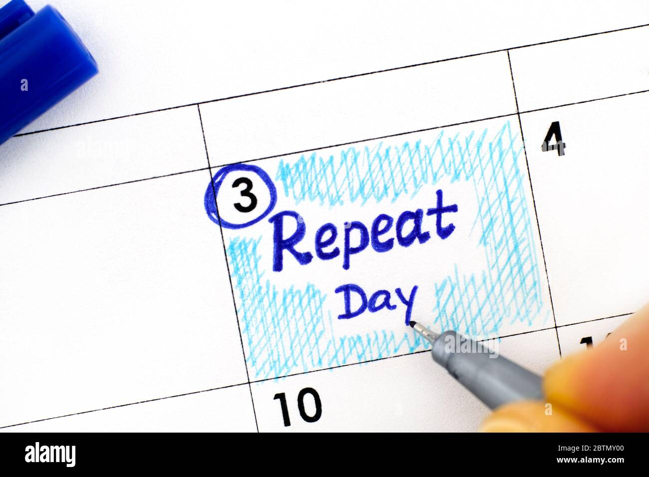 Woman fingers with pen writing reminder Repeat Day in calendar. June 03. Stock Photo