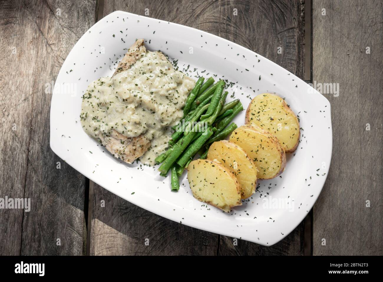 chicken breast with blue cheese sauce and roast potatoes with green beans on rustic old wood background Stock Photo