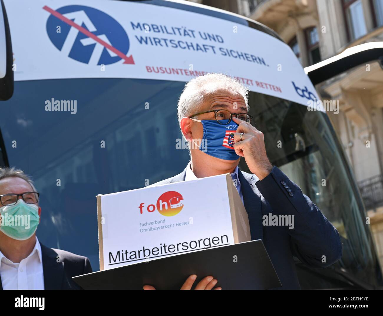 """Wiesbaden, Germany. 27th May, 2020. Tarek Al-Wazir (Bündnis 90/Die Grünen), Minister of Economics of the State of Hesse, stands in front of a coach with the inscription """"Sichern Mobilität und Witschaft sichern. Bus companies now save"""". The bus companies are calling for immediate aid because of the Corona crisis. About 100 buses from all over Hesse took part in the event. Credit: Arne Dedert/dpa/Alamy Live News Stock Photo"""