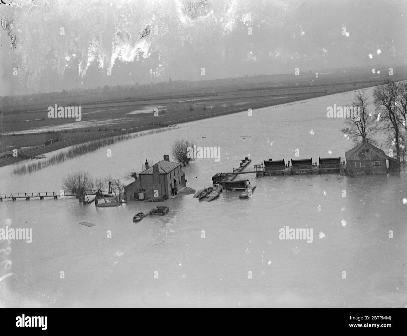 Picture from the air . Floods grow worse in Fen Country . Two hundred and fifty square miles of territory are now flooded in the Fen district , and several villages have been evacuated . Desperate efforts are still being made by the tired bands of workers to prevent the situation from growing even worse . Photo shows , a hamlet surrounded by floods between Earith and St Ives , aerial picture . 17 March 1937 Stock Photo