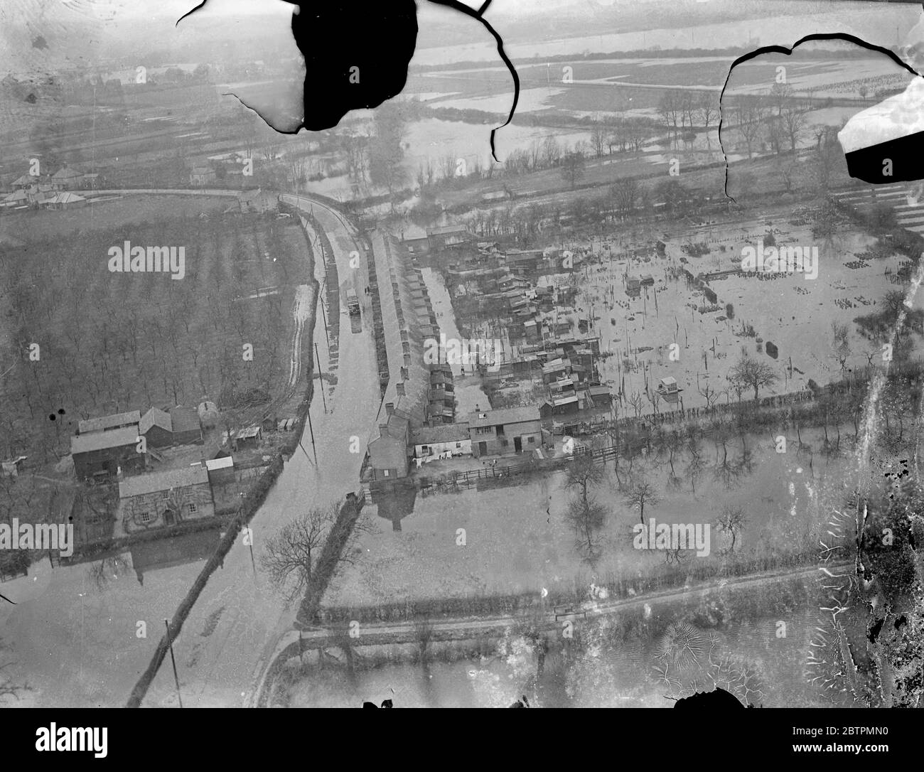 Picture from the air . Floods grow worse in Fen Country . Two hundred and fifty square miles of territory are now flooded in the Fen district , and several villages have been evacuated . Desperate efforts are still being made by the tired bands of workers to prevent the situation from growing even worse . Photo shows , houses surrounded by the floods near Earith . 17 March 1937 Stock Photo