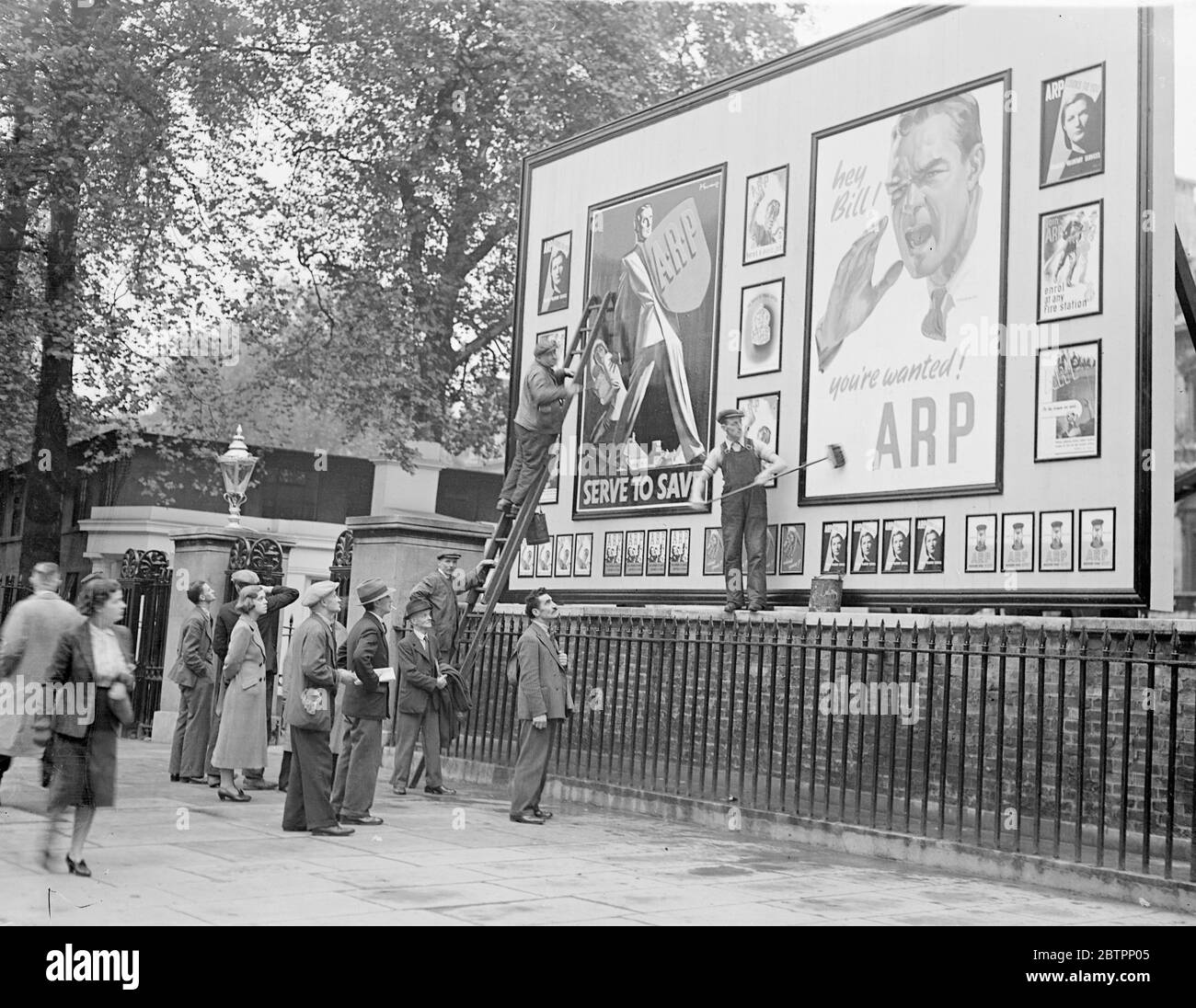 ARP volunteers still wanted. Although the prospects of settling the Sudetenland dispute are now brighter, air raid precautions work is still going on at full pressure in London as a safety measure. Photo shows, workers on their way to business paused to watch the new ARP posters being plastered up in Whitehall. 29 September 1938 Stock Photo