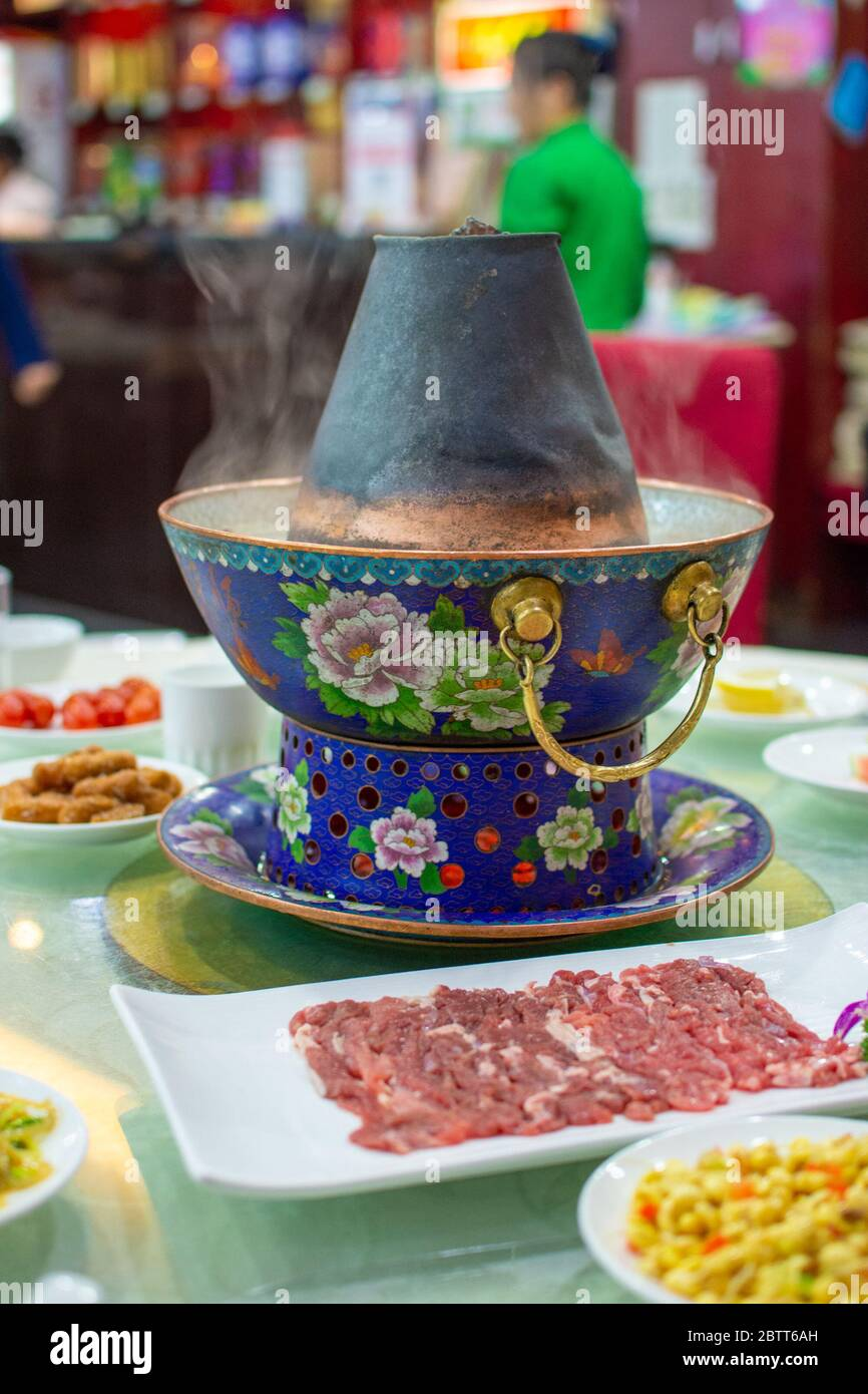 Beijing / China - December 31, 2015: Traditional Beijing style Chinese coal-heated brass hot pot placed at the center of the dining table at a restaur Stock Photo