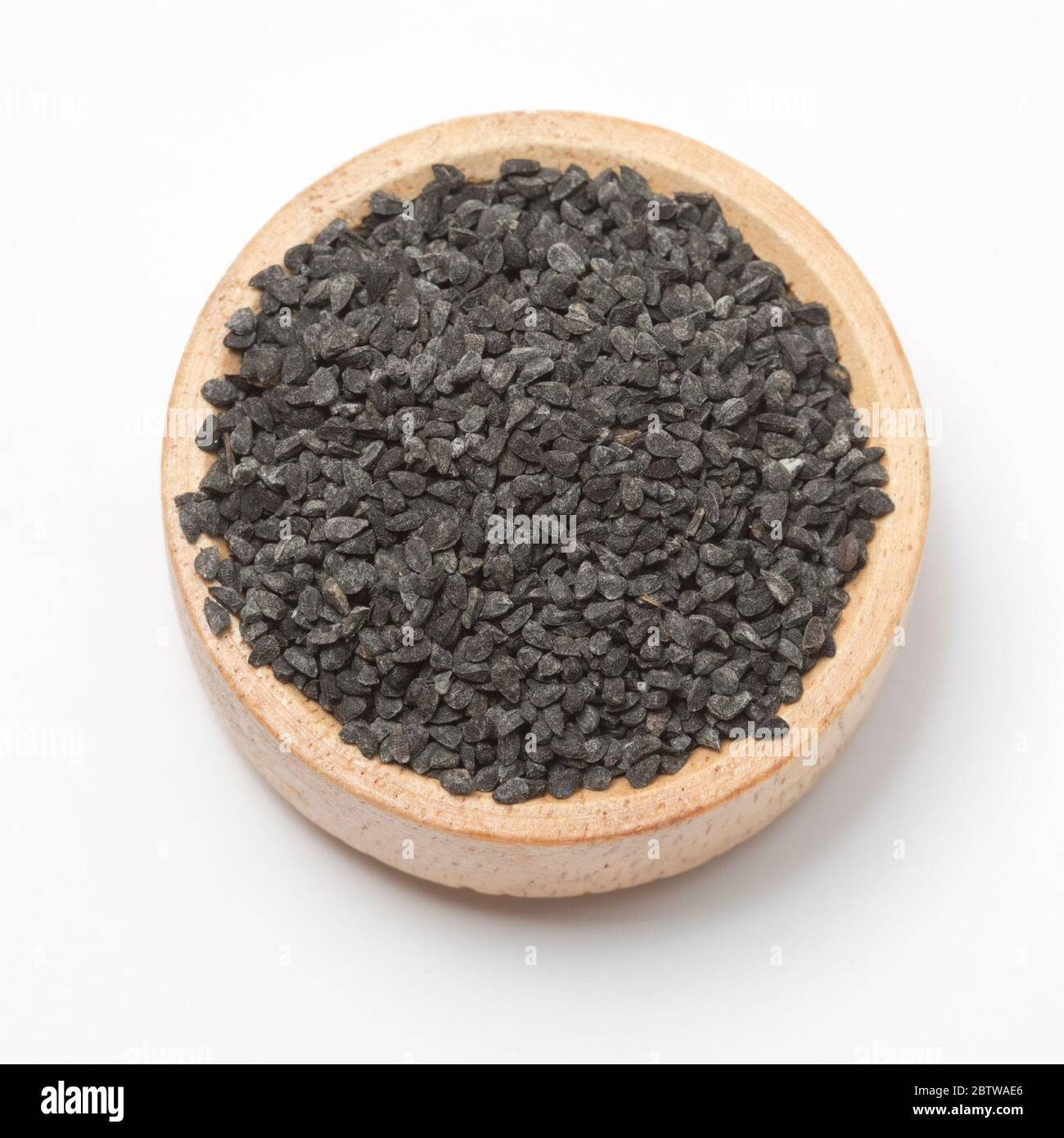 Close-up view of raw black cumins in a small wooden bowl on white background. Stock Photo