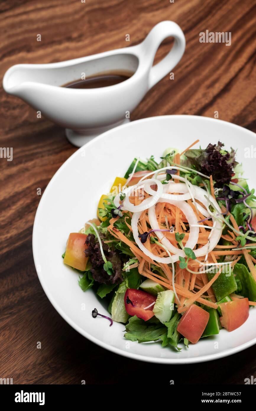 fresh organic mixed vegetable vegan Garden Salad with Vinaigrette sauce on wooden table Stock Photo