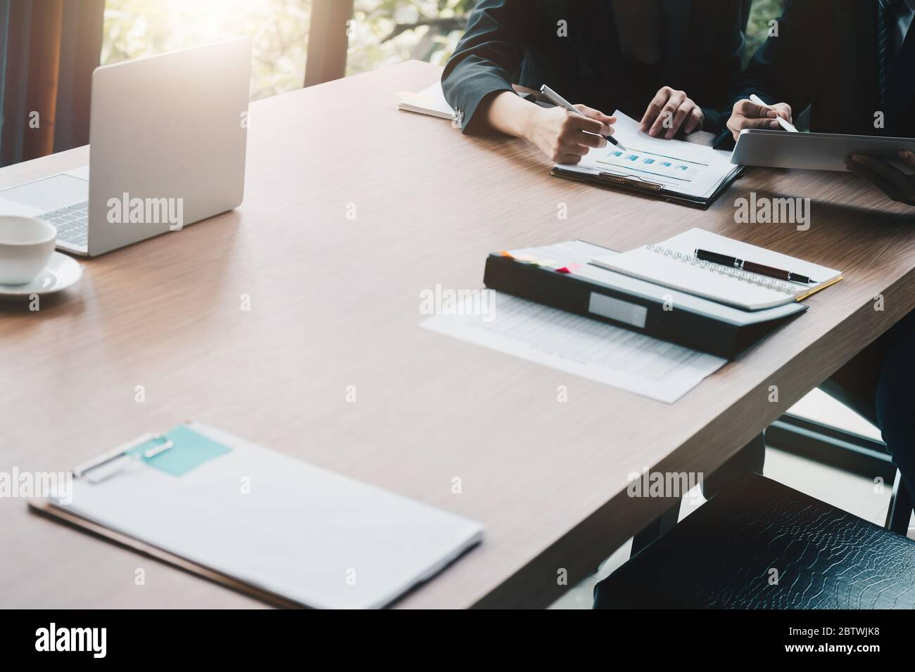 Group of business people busy discussing financial matter during meeting. Corporate Organization Meeting Concept Stock Photo