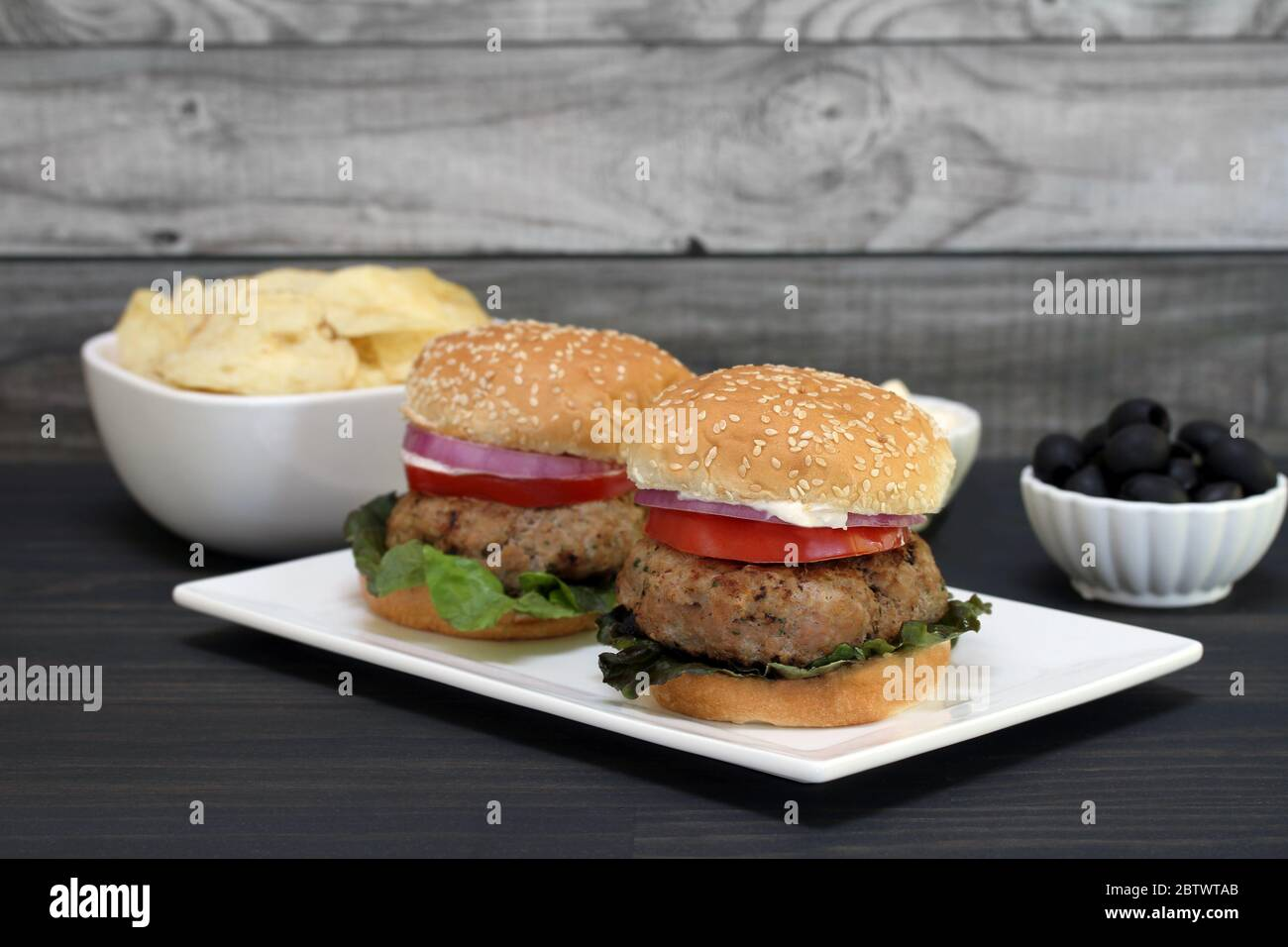 Two Healthy Turkey Burgers On A Rectangular Platter Burgers Are Garnished With Red Leaf Lettuce Onion And Sauce Selective Focus On Front Burger Stock Photo Alamy
