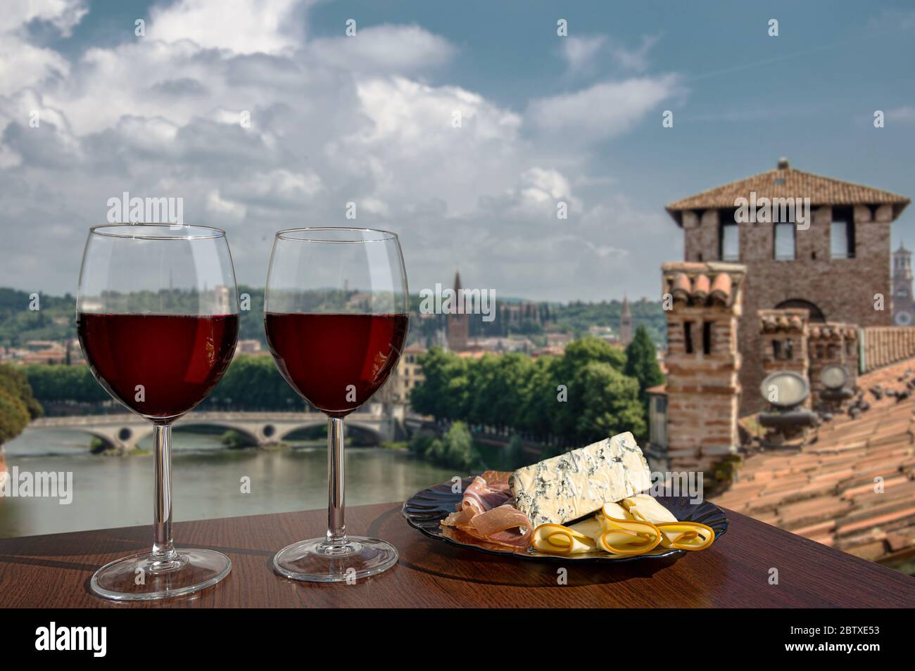 Two glasses of wine with charcuterie assortment on view of Verona, Italy. Glass of red wine with different snacks - plate with ham, sliced, blue chees Stock Photo