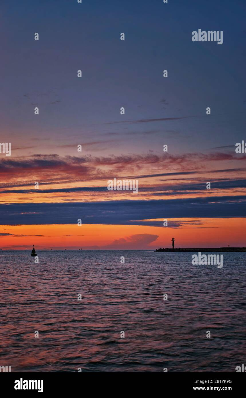 Baltic Sea with lighthouse in the evening in Swinemünde. Swinoujscie, Poland Stock Photo