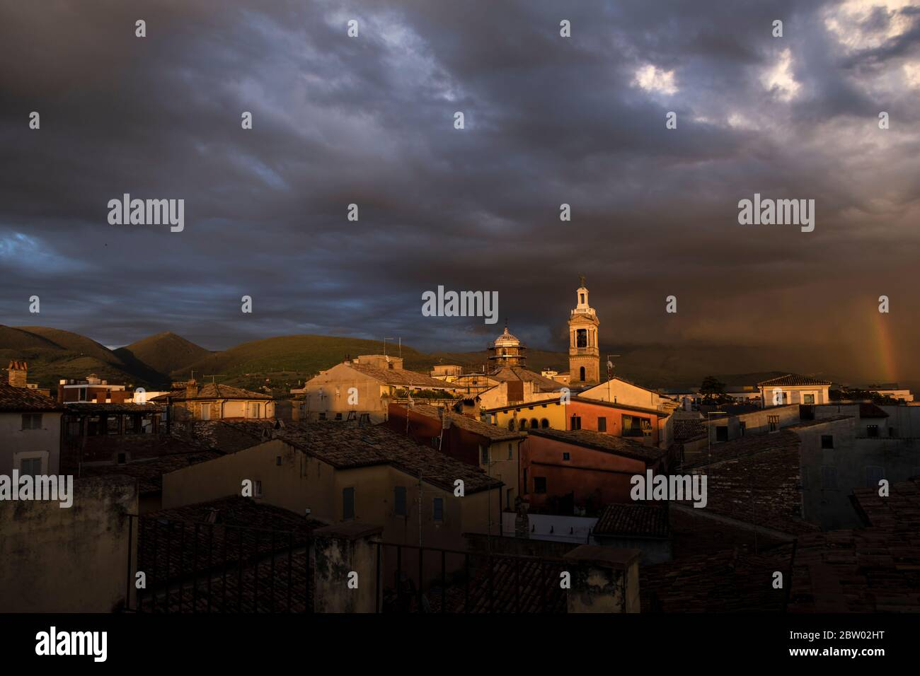 Rooftops of Foligno caught in sunlight, but set against stormy sky with a rainbow.  Umbria, Italy Stock Photo