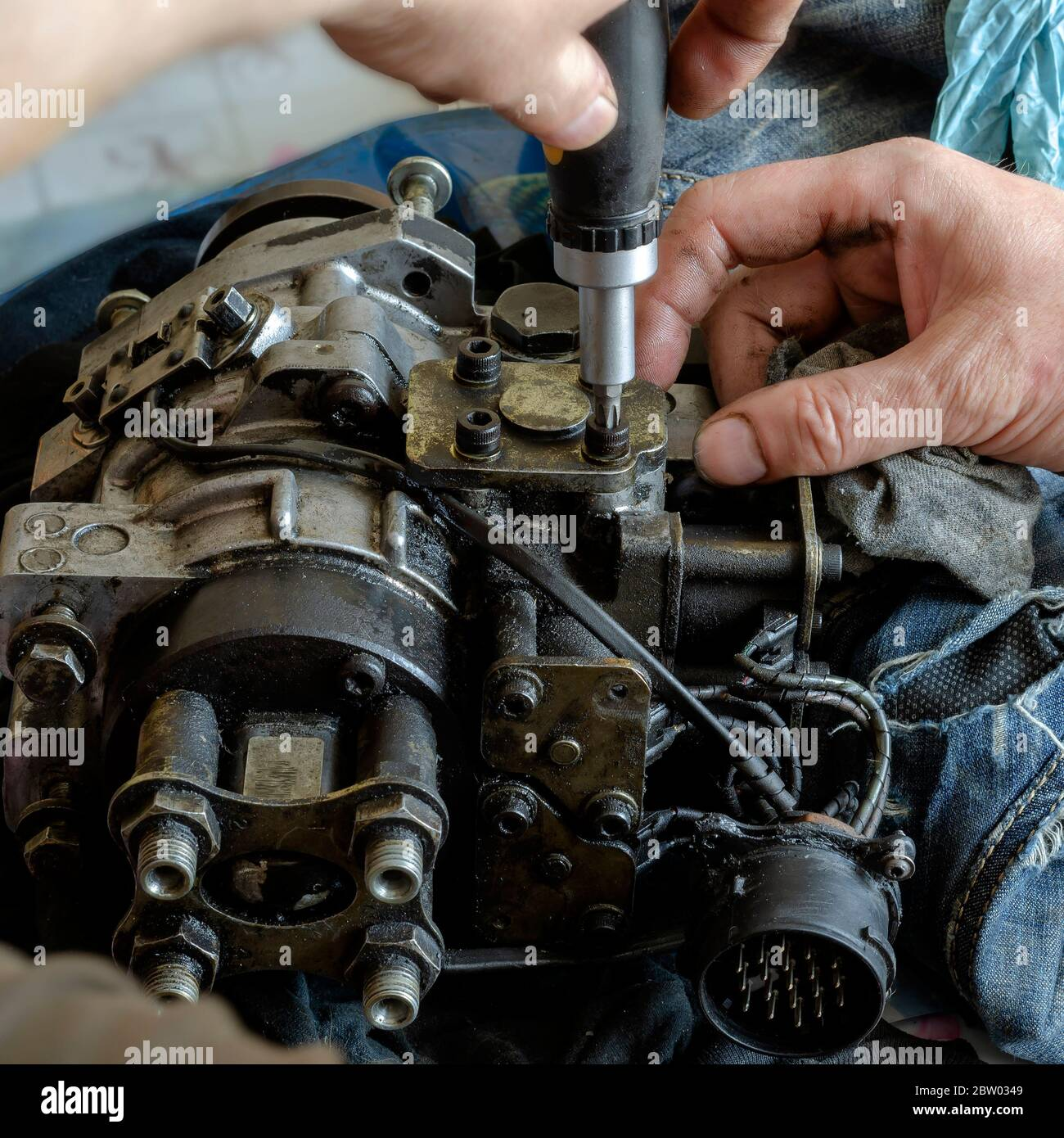 A mechanic disassembles and detects a fuel injection pump. The process of repairing the fuel pump of a diesel car in the workshop. Car service. Select Stock Photo