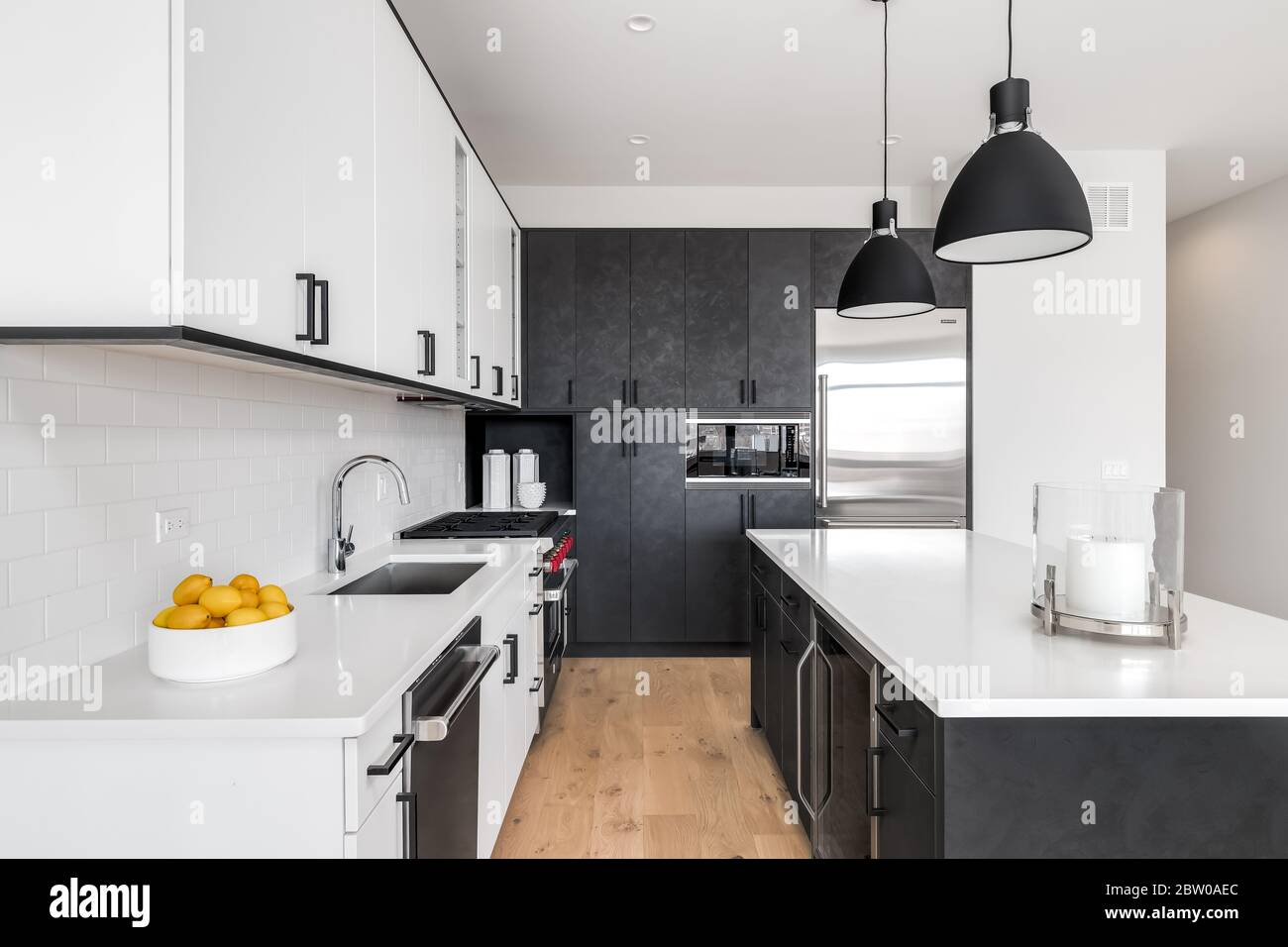 - A Modern Kitchen With Black And White Cabinets, Stainless Steel