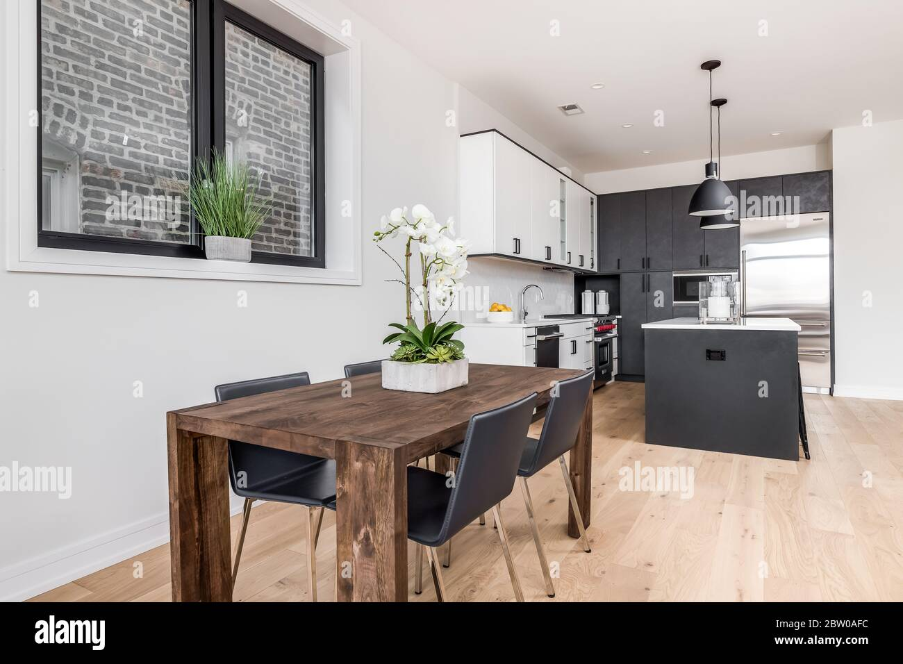 A Dining Room And Kitchen With White And Dark Grey Kitchen Cabinets A Flower Is On The Table As A Centerpiece With Four Chairs At The Wooden Table Stock Photo Alamy