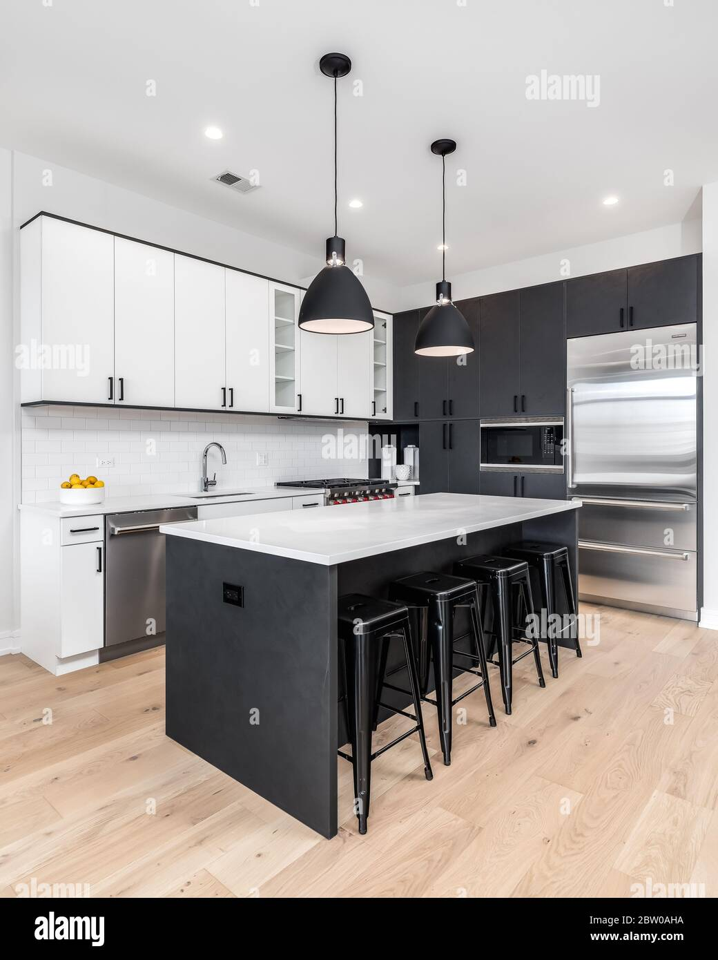 A Modern Kitchen With Black And White Cabinets Stainless Steel Wolf And Sub Zero Appliances And Bar Stools Sitting At The White Granite Counter Top Stock Photo Alamy
