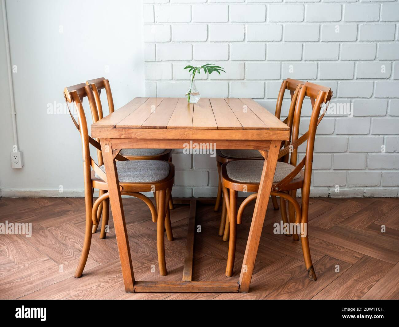 Wooden Dining Table And Four Chairs With Green Leaf In Glass Vase On White Wall Background In Restaurant Stock Photo Alamy