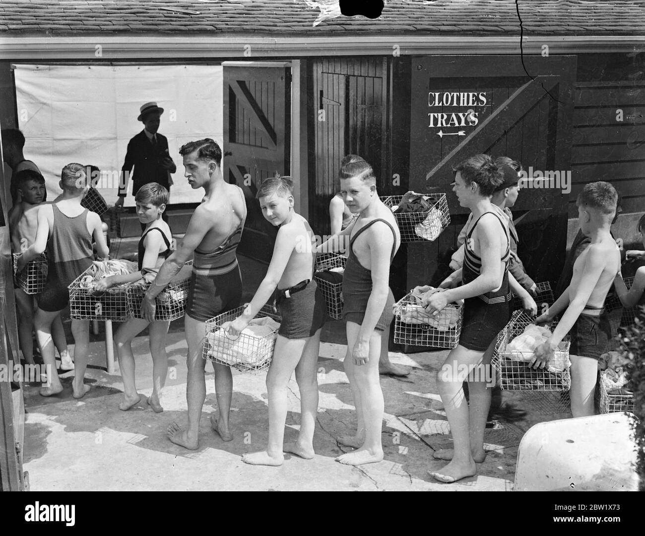 Long queue at Hammersmith open-air baths eight wave refuges. Hundreds of people sought refuge from the heat at the Hammersmith open-air baths. A long queue waited for admission throughout the afternoon. Photo show, bathers with their clothes baskets at the Hammersmith Baths. 29 May 1937 Stock Photo