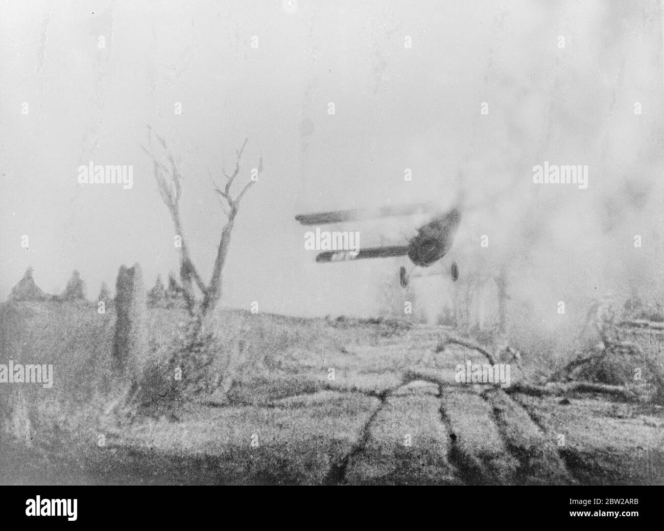 Japanese plane crashes in flames after being shot down by Chinese. This picture, just received in London by air, shows a Japanese plane about to crash in flames in the countryside between Shanghai and Hangchow after having been shot down by the Chinese. The plane is emitting a trial dense smoke as it means the ground. 18 October 1937 Stock Photo